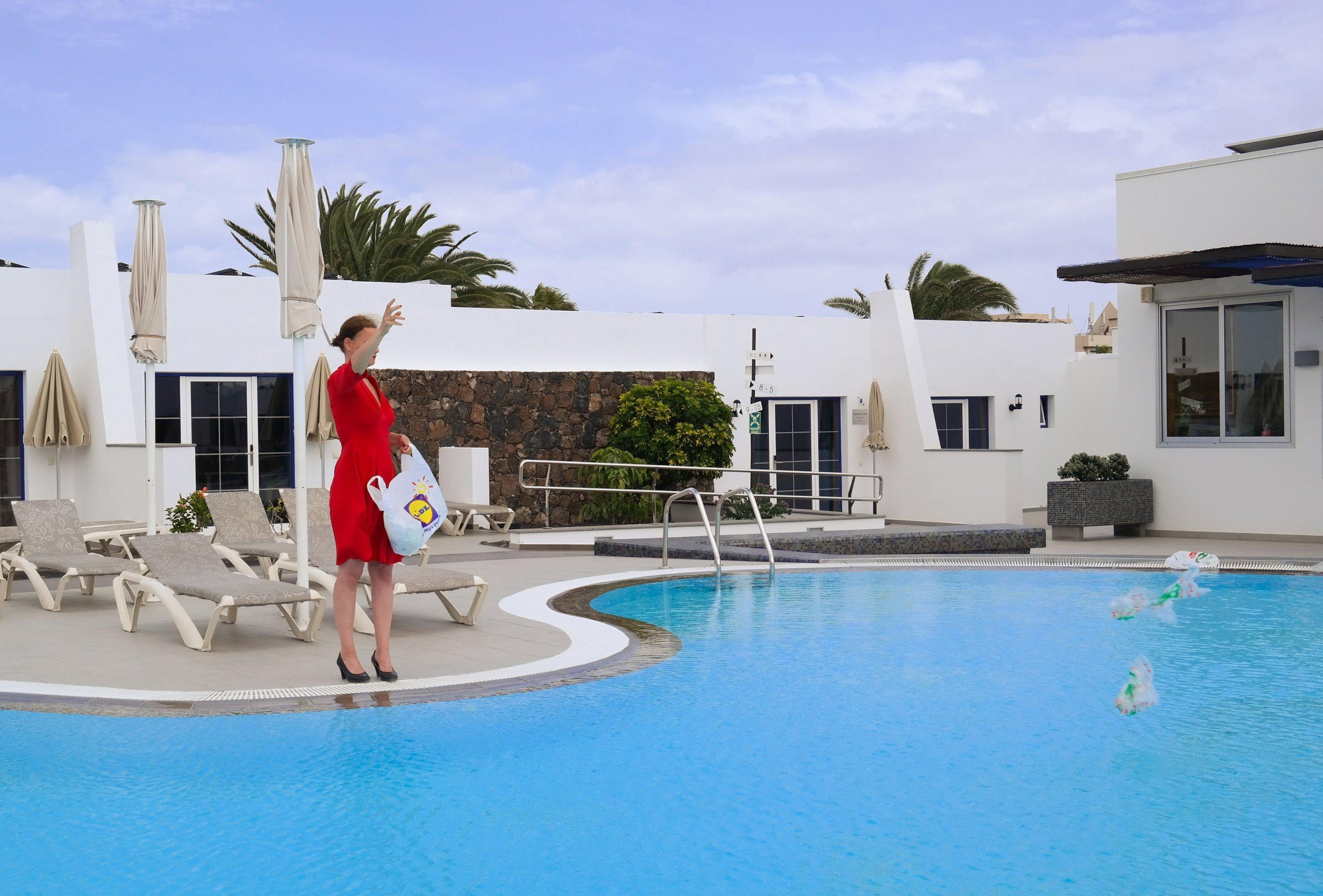 Künstlerin Swaantje Güntzel steht in einem roten Kleid vor einem Pool und wirft aus einer Lidl-Tasche Plastiktüten in diesen.