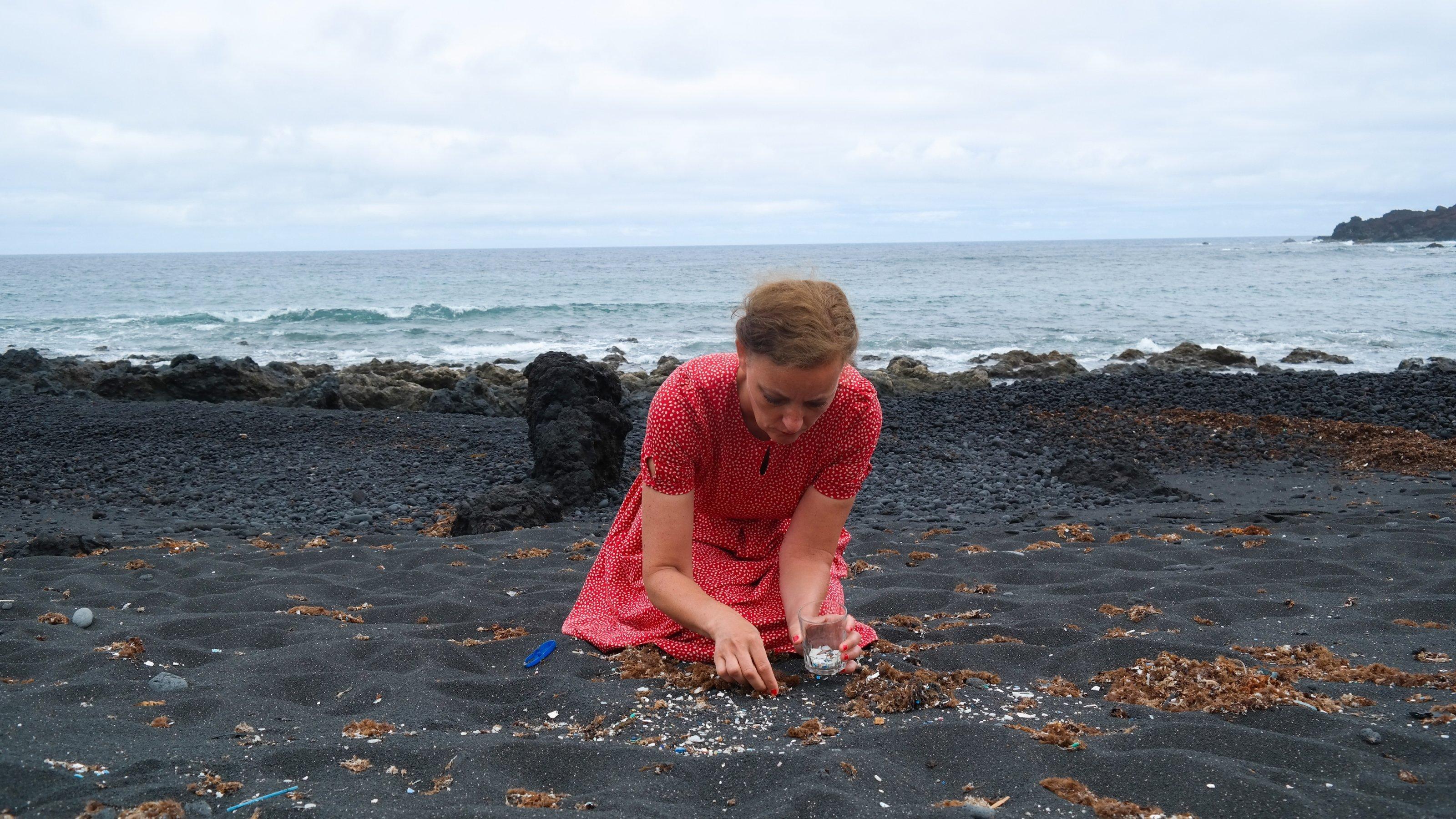 Künstlerin Swaantje Güntzel hockt in einem roten Kleid an einem schwarzen Strand und sammelt Mikroplastik aus dem Sand.