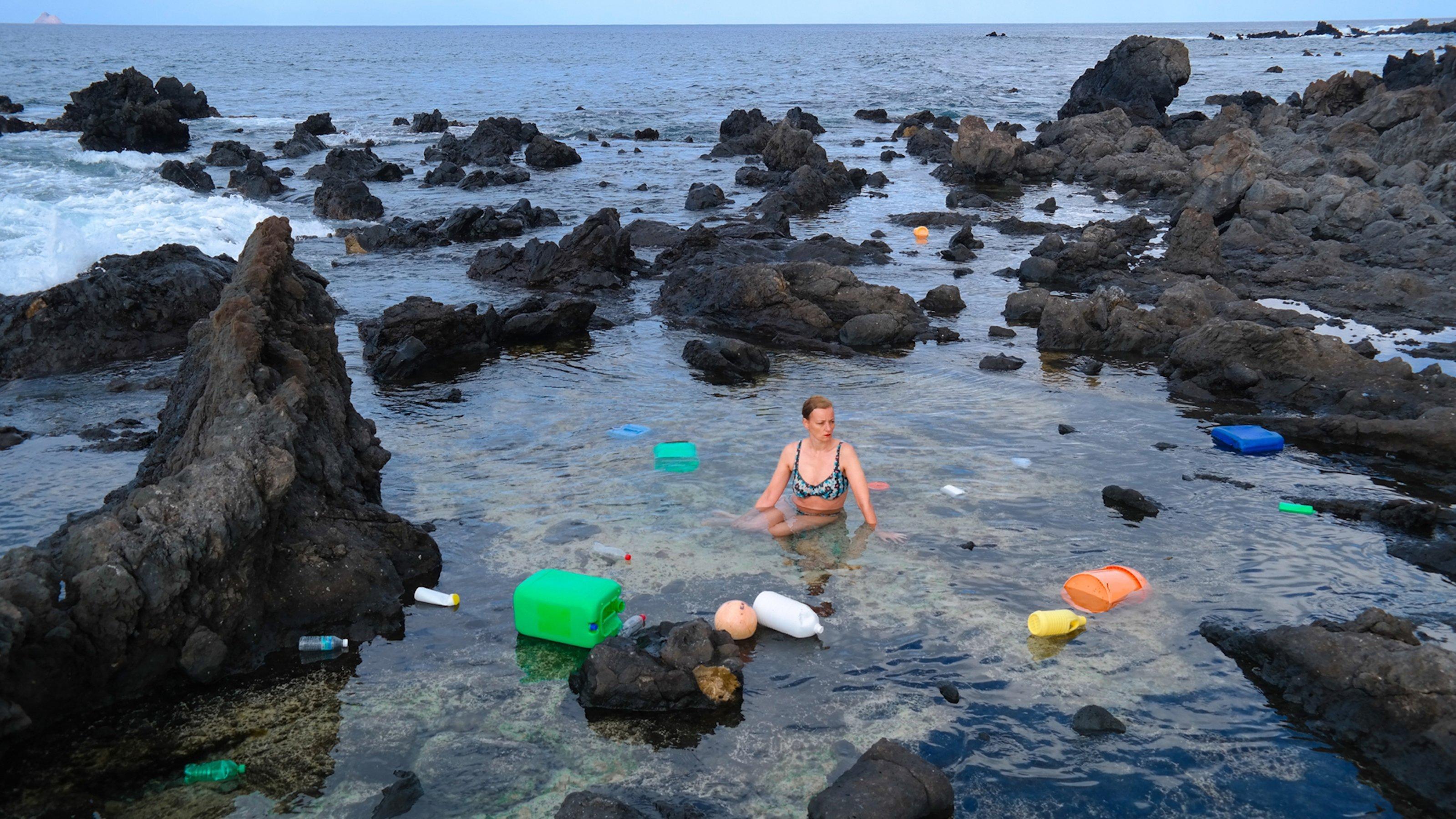 Künstlerin Swaantje Güntzel sitzt im Bikini in einer steinigen Bucht. Um sie herum schwimmen bunte Plastikbehältnisse.