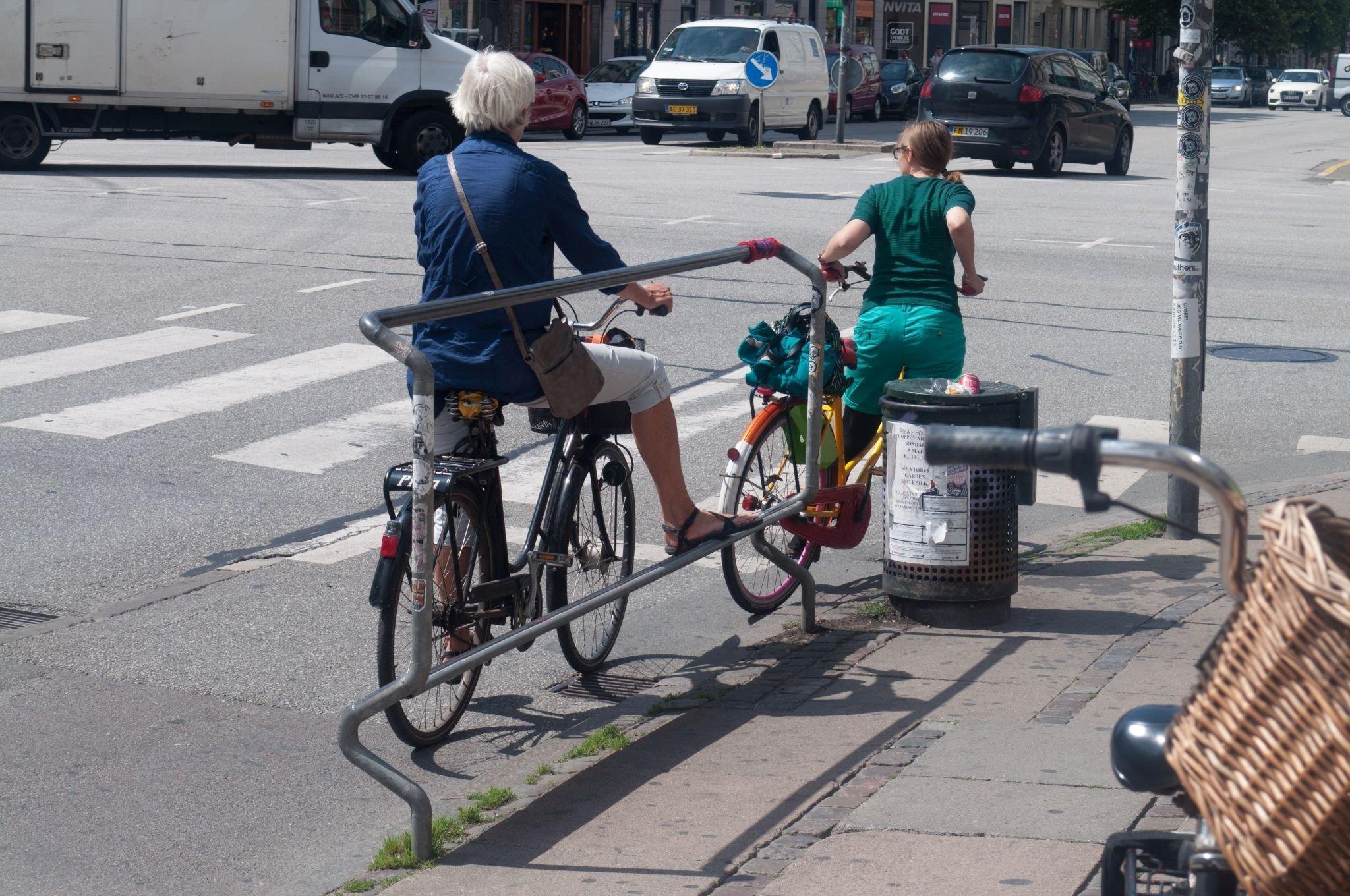 Eine junge Frau hält sich an einer Haltestangen fest. Auf diese Weise muss sie nicht vom Fahrrad absteigen.