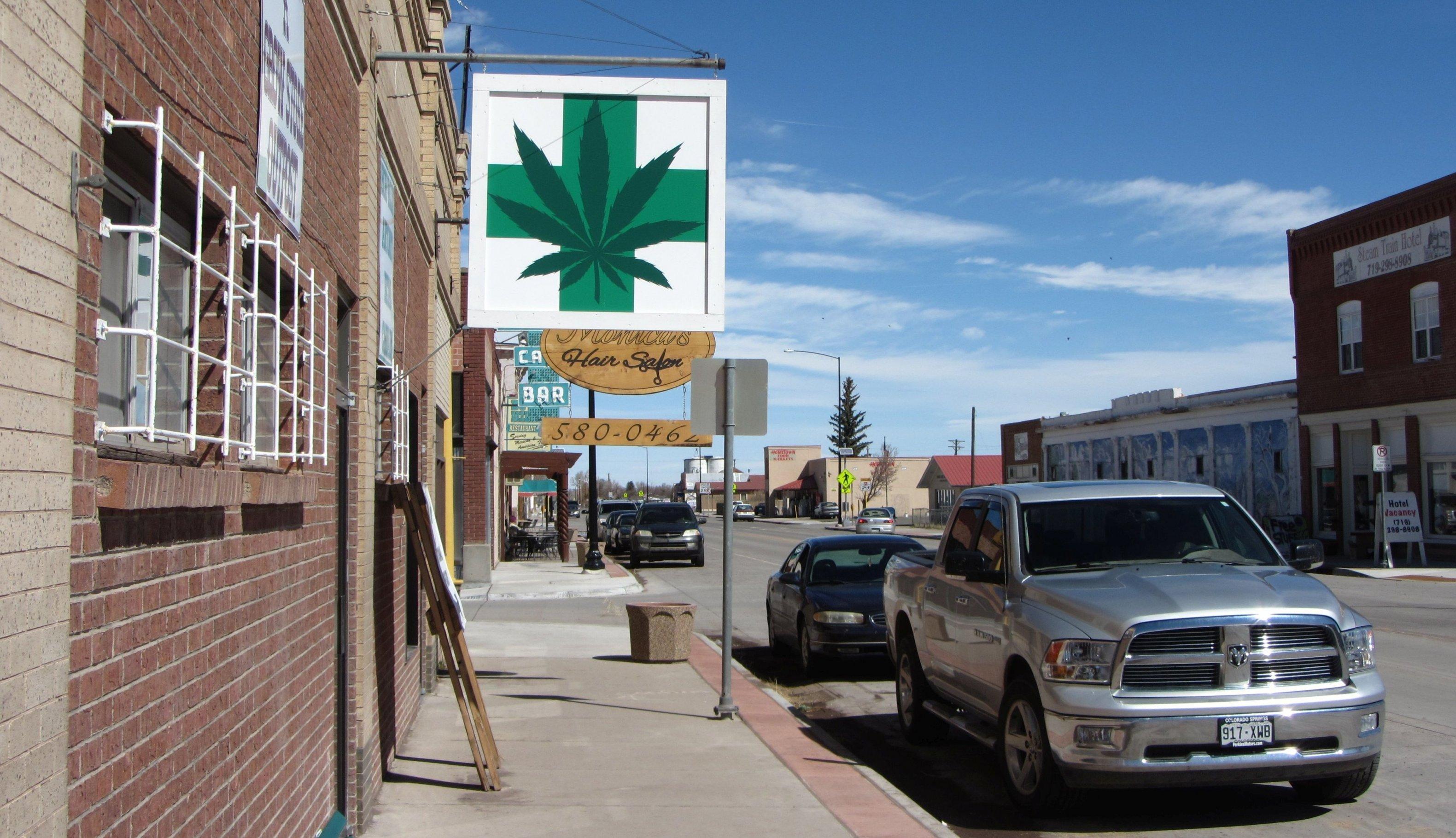Ein vergittertes Ladengeschäft, vor dem eine Fahne mit einem grünen Kreuz und einem Hanfblatt hängt.