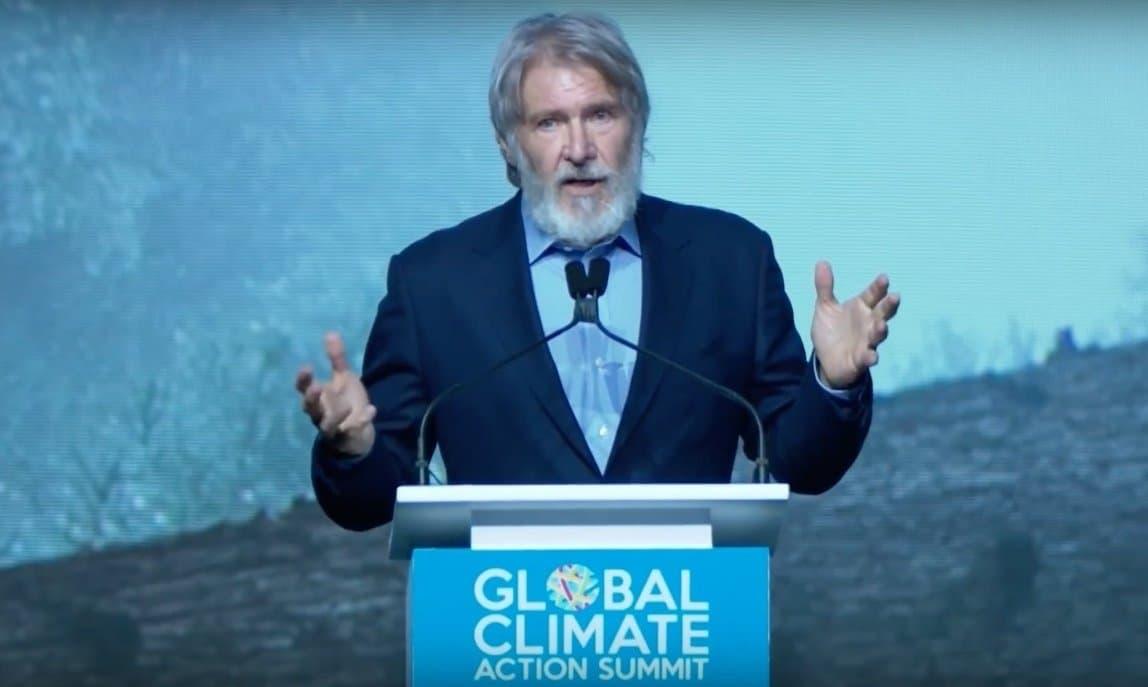 """Der Schauspieler Harrison Ford steht am Rednerpult und unterstreicht seine Worte mit einer großen Geste und angehobenen Händen. In seinem seinem leidenschaftlichen Appell sagt er: """"Wenn wir die Zerstörung unserer natürlichen Welt nicht stoppen können, spielt alles andere keine Rolle mehr."""""""