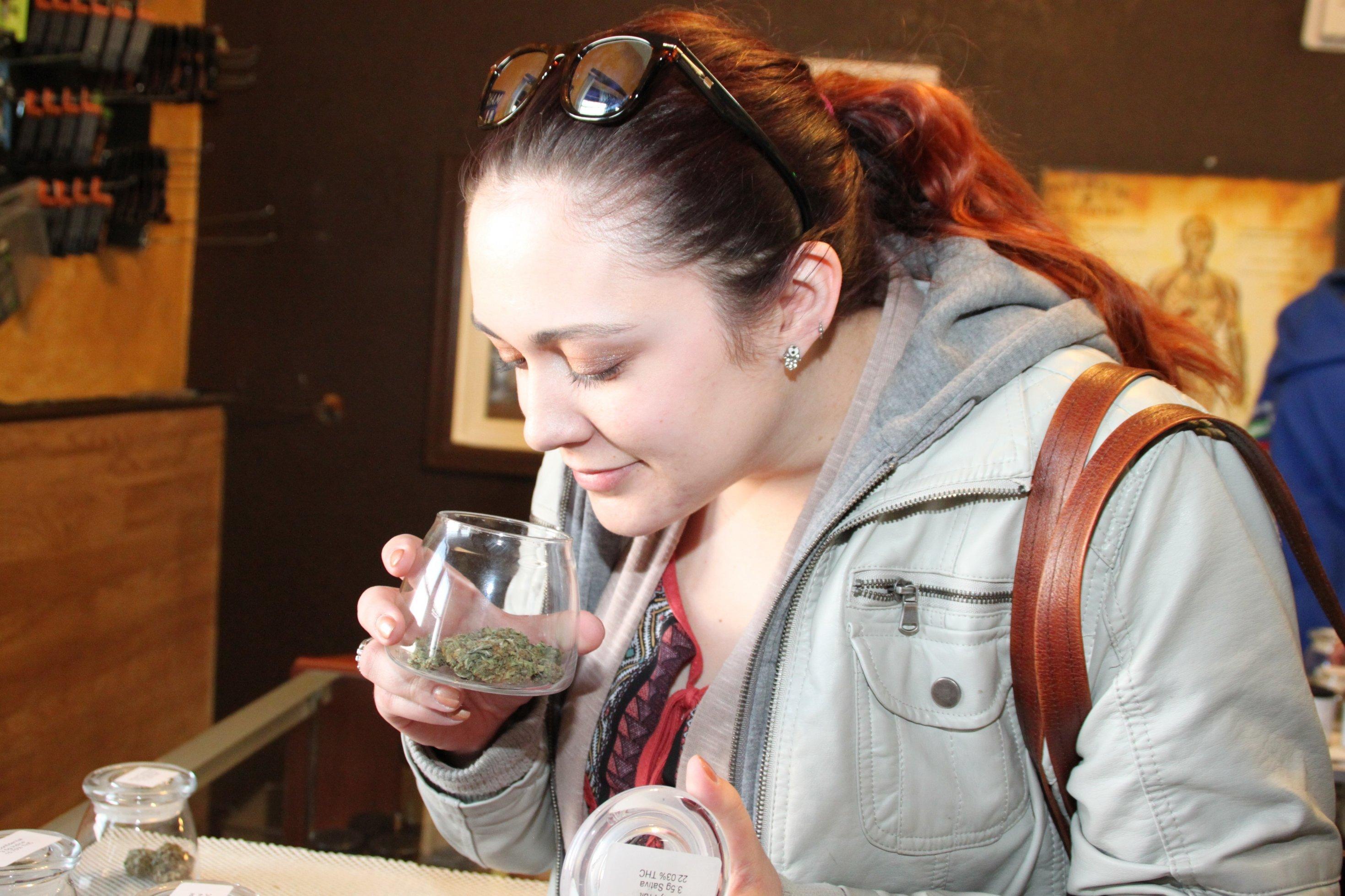Eine junge Frau riecht an einer Dose mit Haschkeksen.