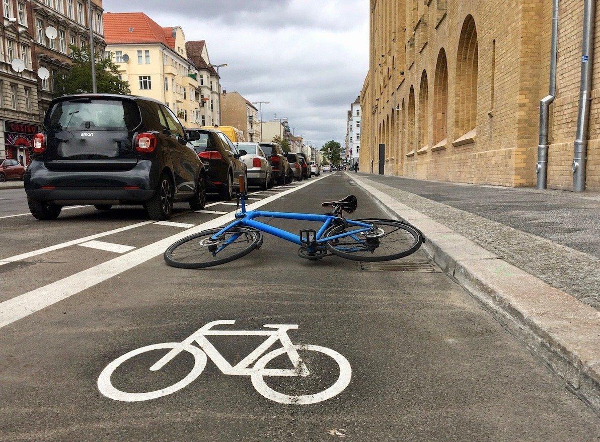 Eine Fahrradspur auf einer Straße mit parkendem Autos. Im Vordergrund ist das Piktogramm eines Fahrrades zu sehen, direkt dahinter liegt ein materielles, blaues Sportrad.