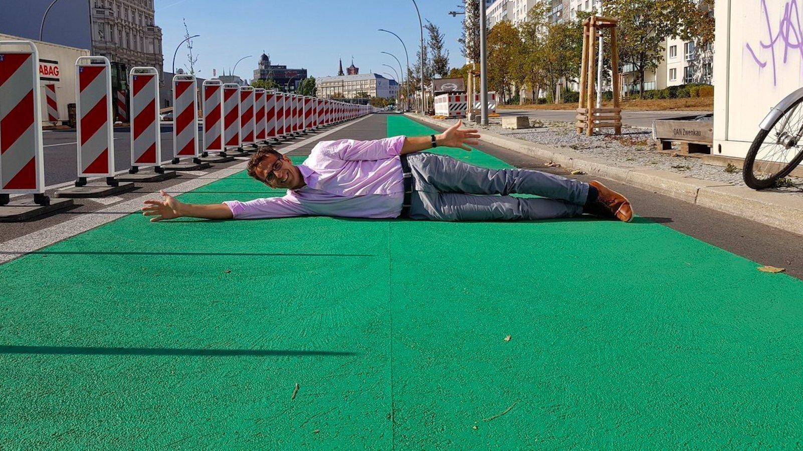 Der Mann liegt quer mit ausgestreckten Armen auf einem grünen Radweg und lächelt in die Kamera. Der Himmel ist blau.