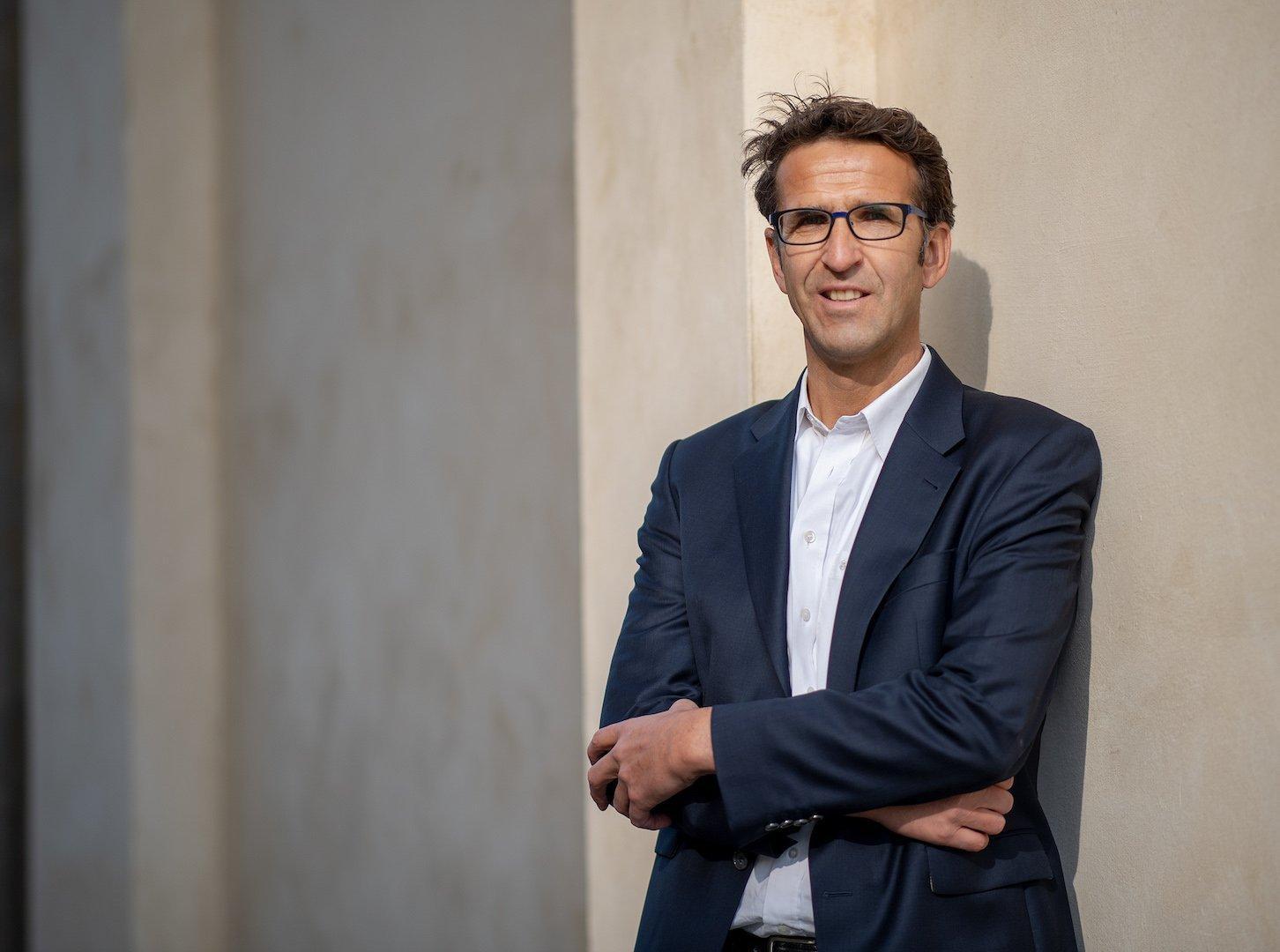 Ein Mann mit kurzen braunen Haaren steht in blauem Anzug und weißem Hemd mit verschränkten Armen vor einer Wand. Er trägt eine Brille.