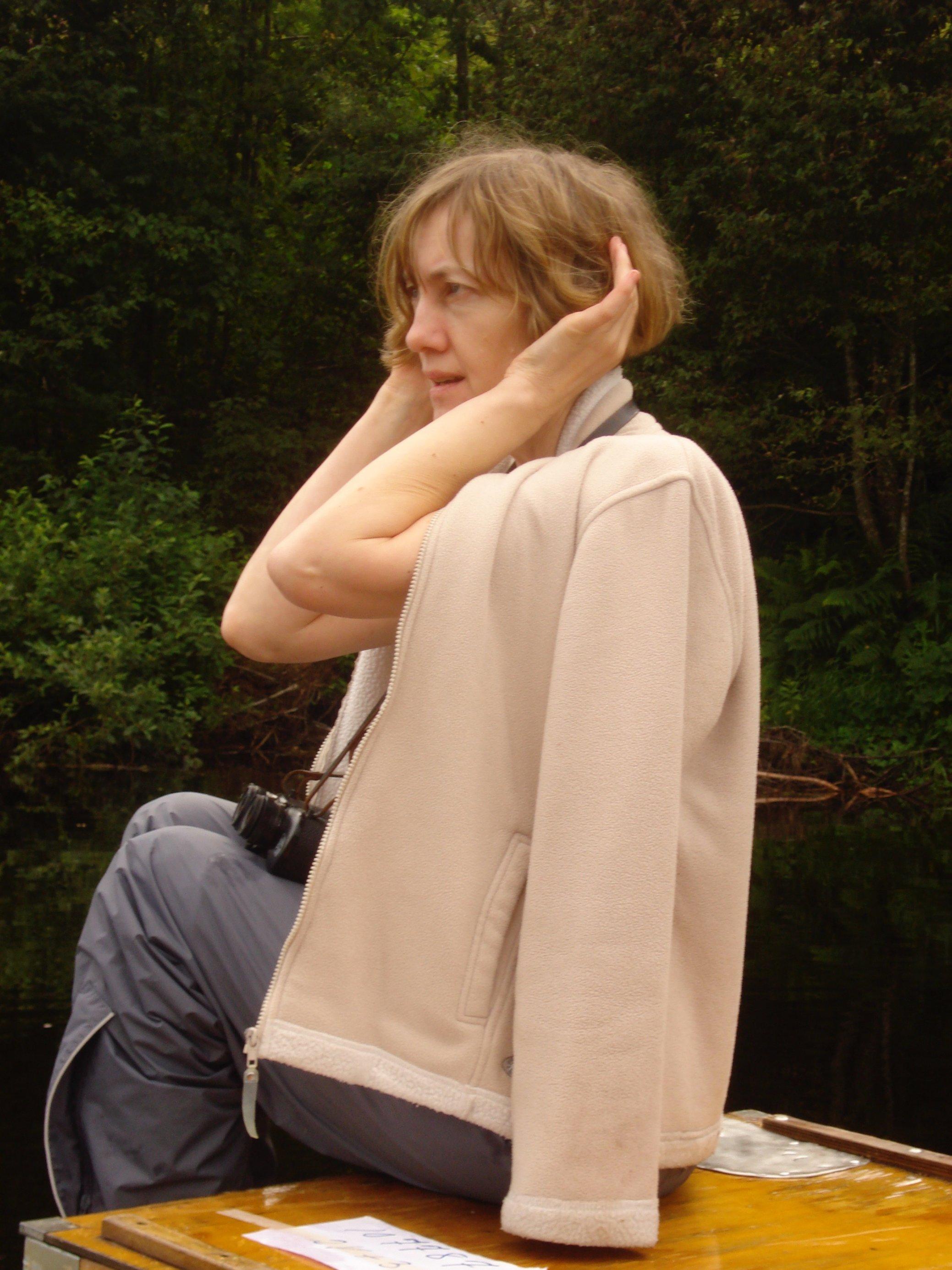 Flugbegleiterin Johanna Romberg hält sich beide Hände hinter die Ohren, um die Vogelstimmen in einem Wald zu idenfitizieren.