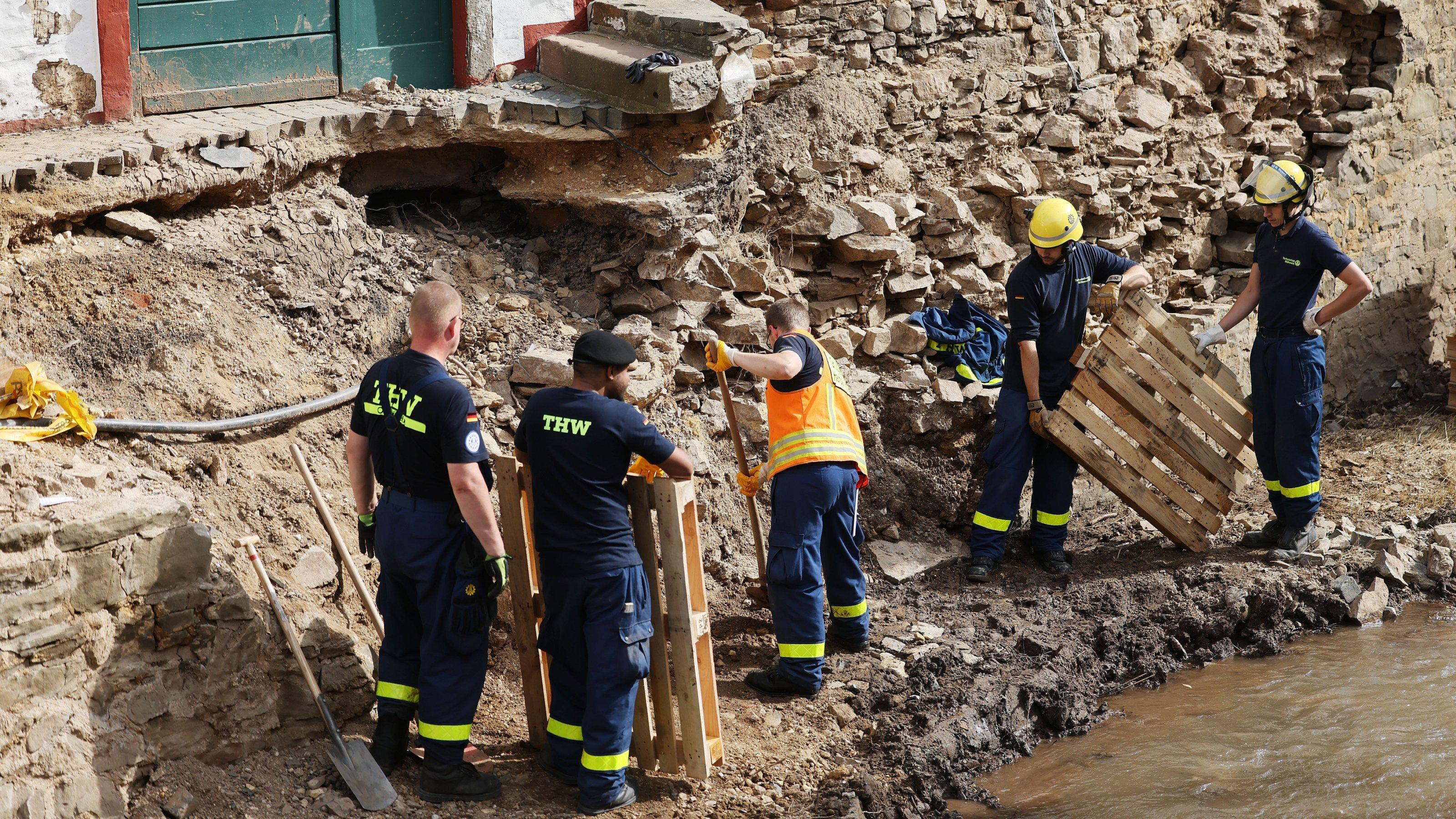 Helfer des THW arbeiten an der Absicherung eines Gebäudes an der Erft. Das Hochwasser hat erhebliche Schäden in der Eifel angerichtet.