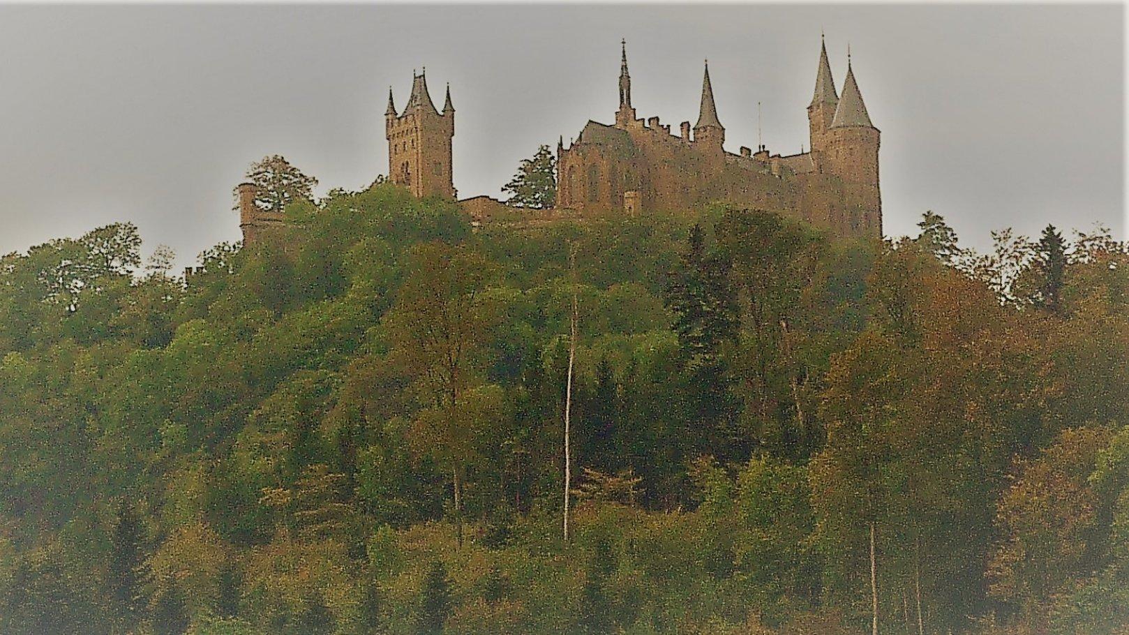 Über den steilen, dicht bewaldeten Hängen südlich der Ortschaft Boll ragen die Giebel und Zinnen der turmbewehrten Burg auf.