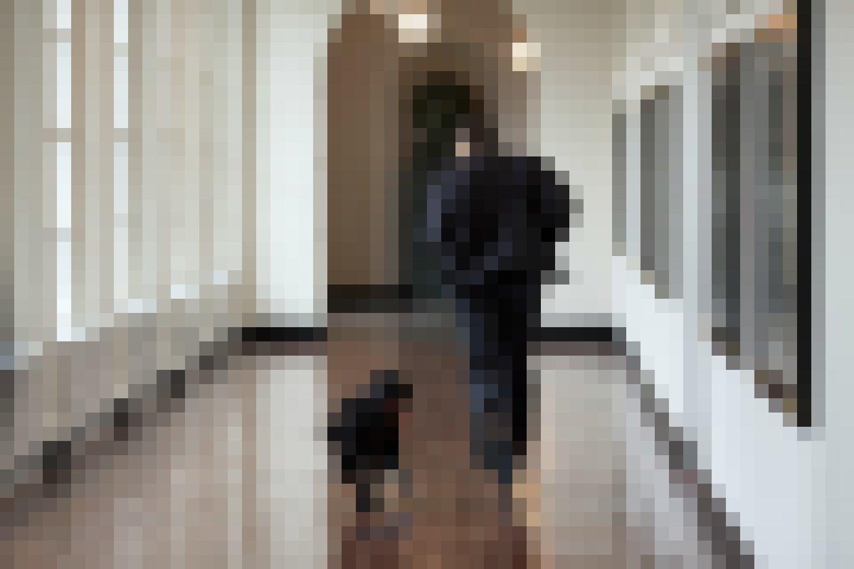 Ein Mann und ein Hund rennen einen Gang entlang.