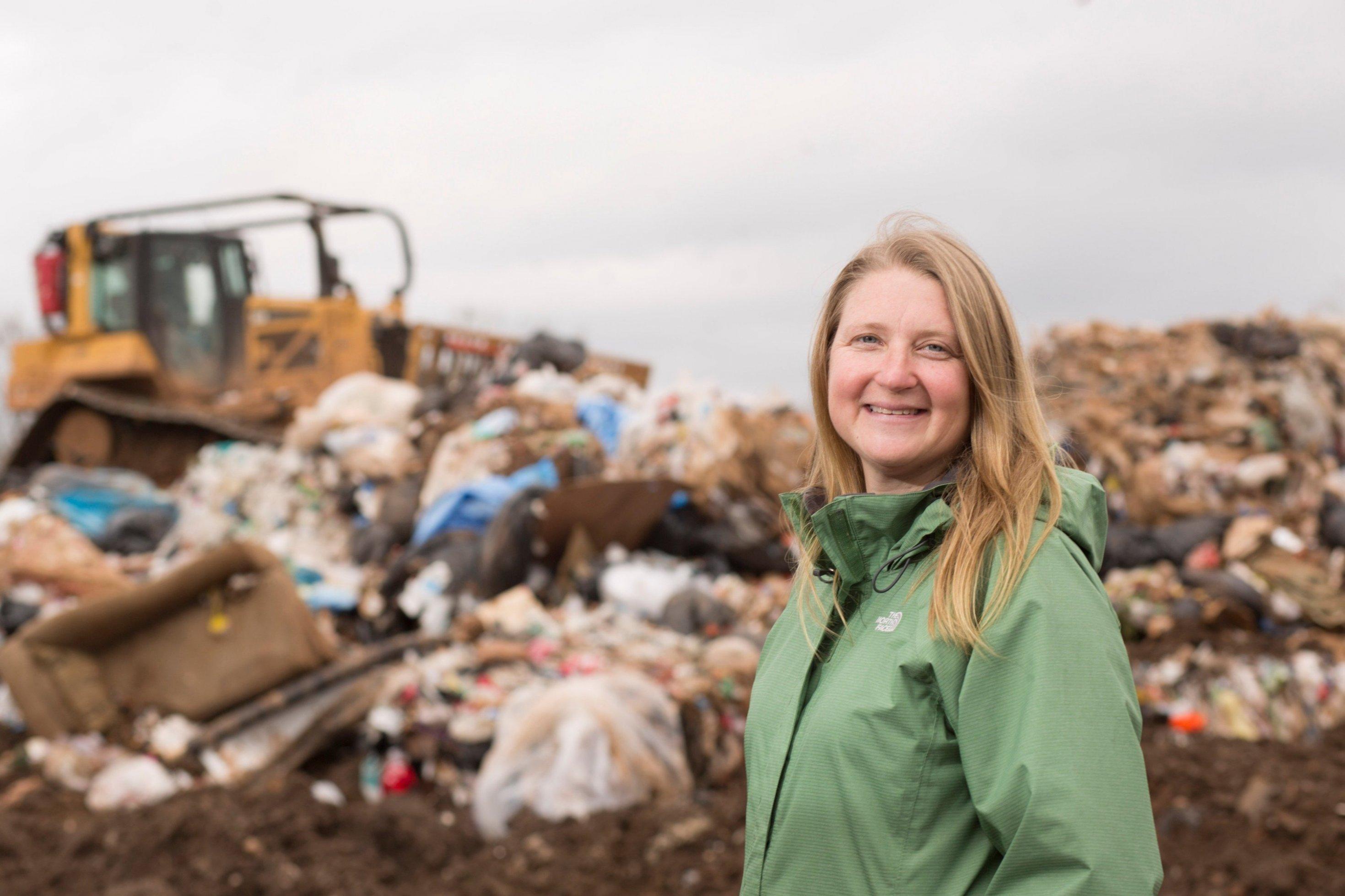 Umweltingenieurin Jenna Jambeck steht in grüner Jacke vor einer Mülldeponie und einem Bagger. Sie lächelt in die Kamera.