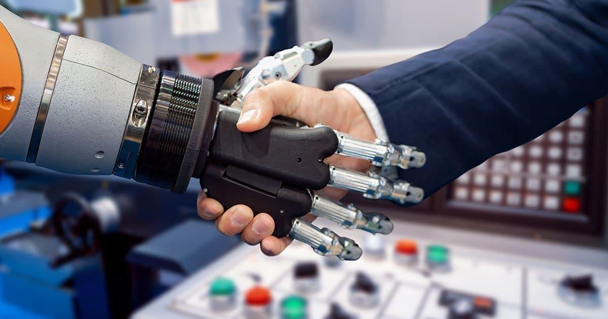 Eine menschliche Hand schütttelt eine Roboterhand