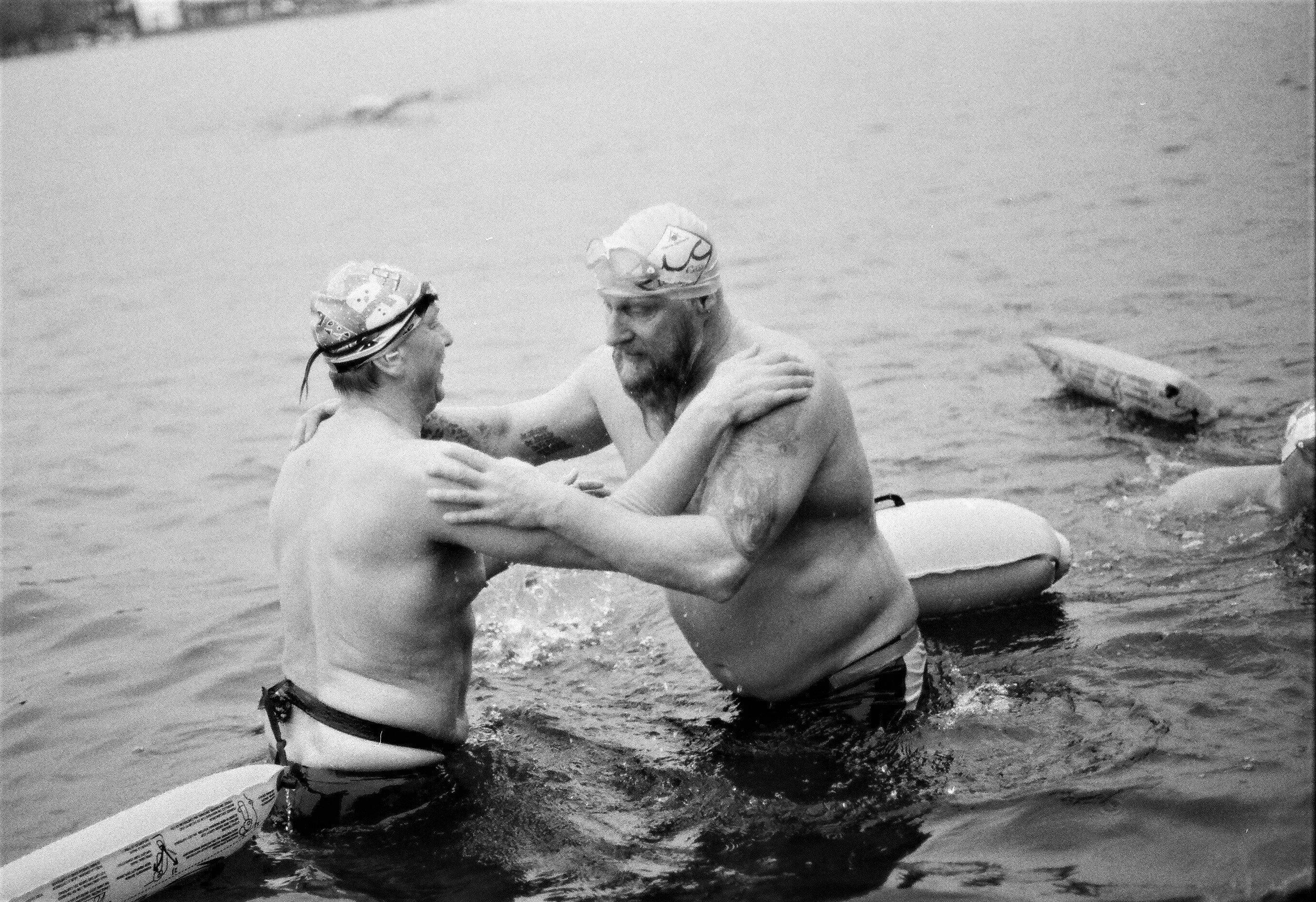 Zwei Männer nur in Badehose im eiskalten Wasser stehend.