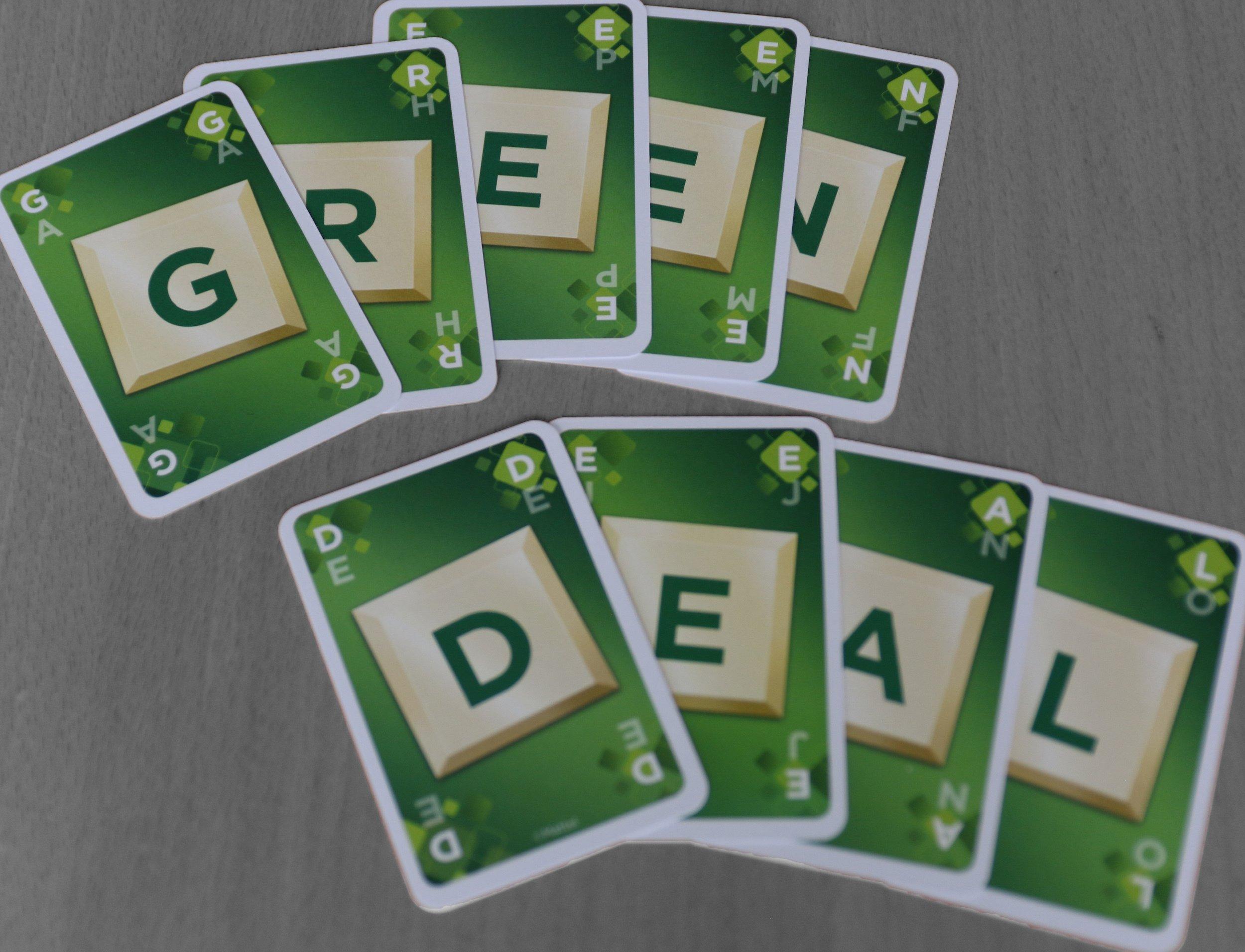 """Auf einem Tisch liegen neun Karten mit Buchstaben, die zusammen """"Green Deal"""" buchstabieren. Während die Karten farbig und vor allem grün sind, ist die Tischoberfläche schwarz-weiß gehalten. – Der europäische Green Deal soll nach den Forderungen vieler Expert*innen aus Politik, Industrie und Zivilgesellschaft die graue Wirtschaft in eine grüne überführen."""
