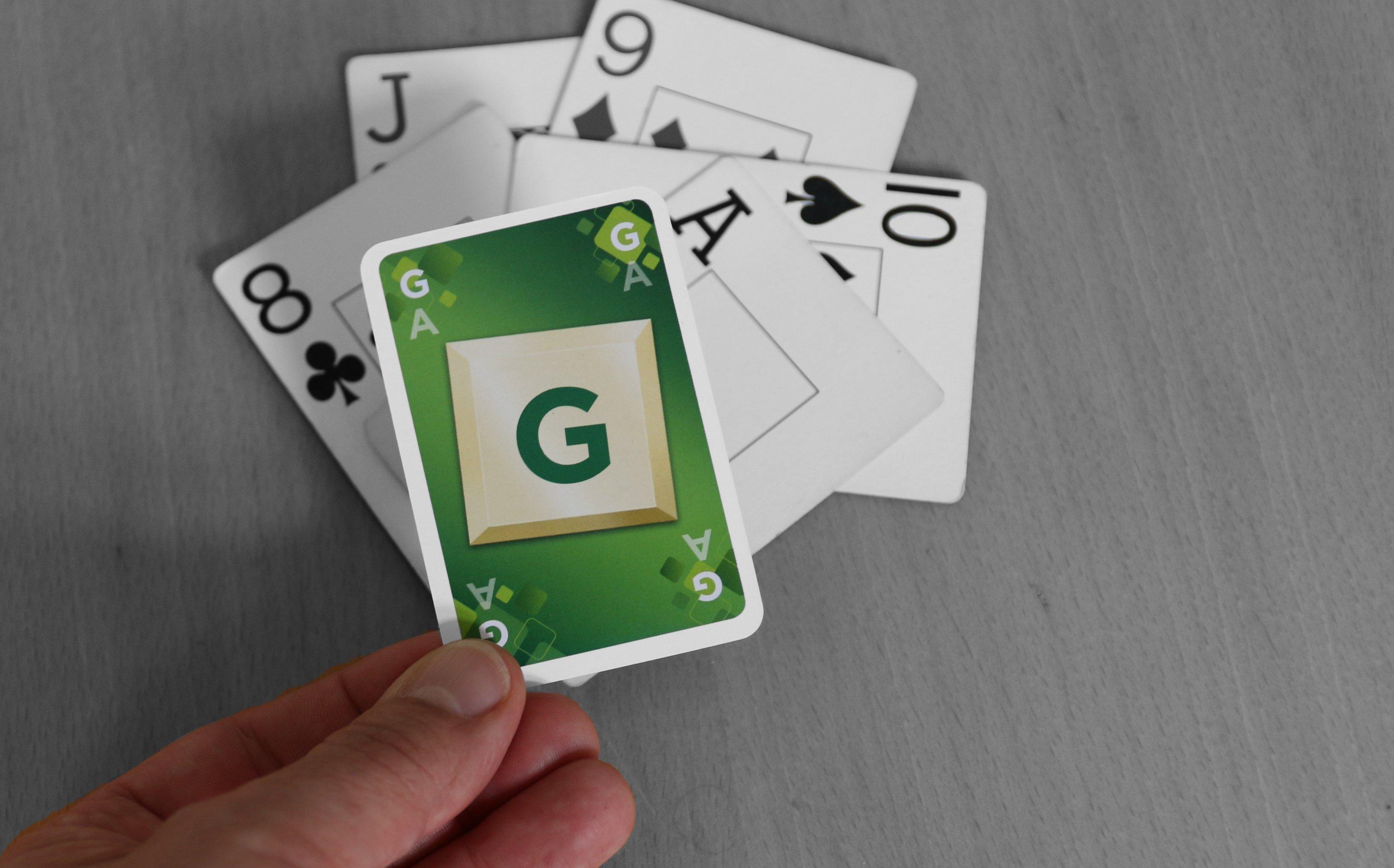 Auf einen Tisch liegen fünf Spielkarten. Eine Hand legt eine sechste Karte darauf. Sie gehört aber nicht zu einem normalen Kartenspiel, sondern ist leuchtend grün und zeigt ein großes G. Die Tischoberfläche und die Karten darauf sind hingegen in schwarz-weiß gehalten. – Ein grüner Trumpf für einen grauen Stich.