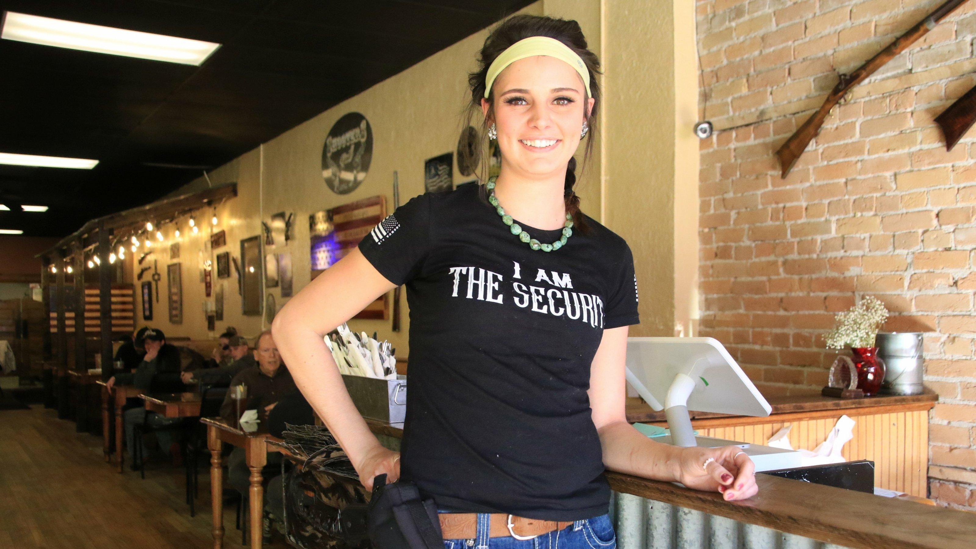 Eine junge Frau, die eine Pistole am Gürtel trägt, lehnt an einem Tresen. In Hintergrund hängen Gewehre.