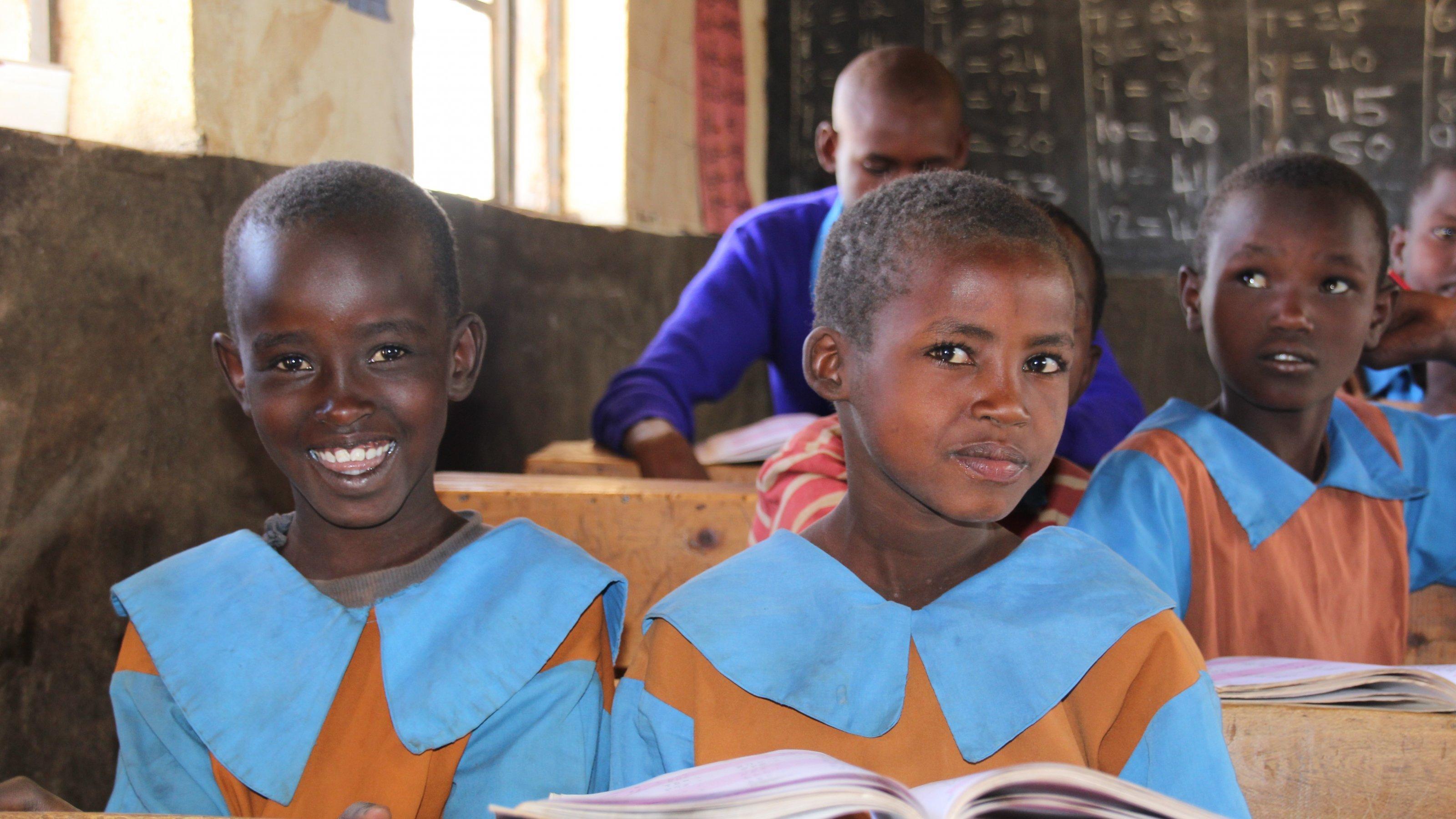 Schülerinnen und Schüler sitzen in blauen Schuluniformen in Holzbänken, gucken in die Kamera. Im Hintergrund ist die Tafel mit Rechenaufgaben zu sehen.