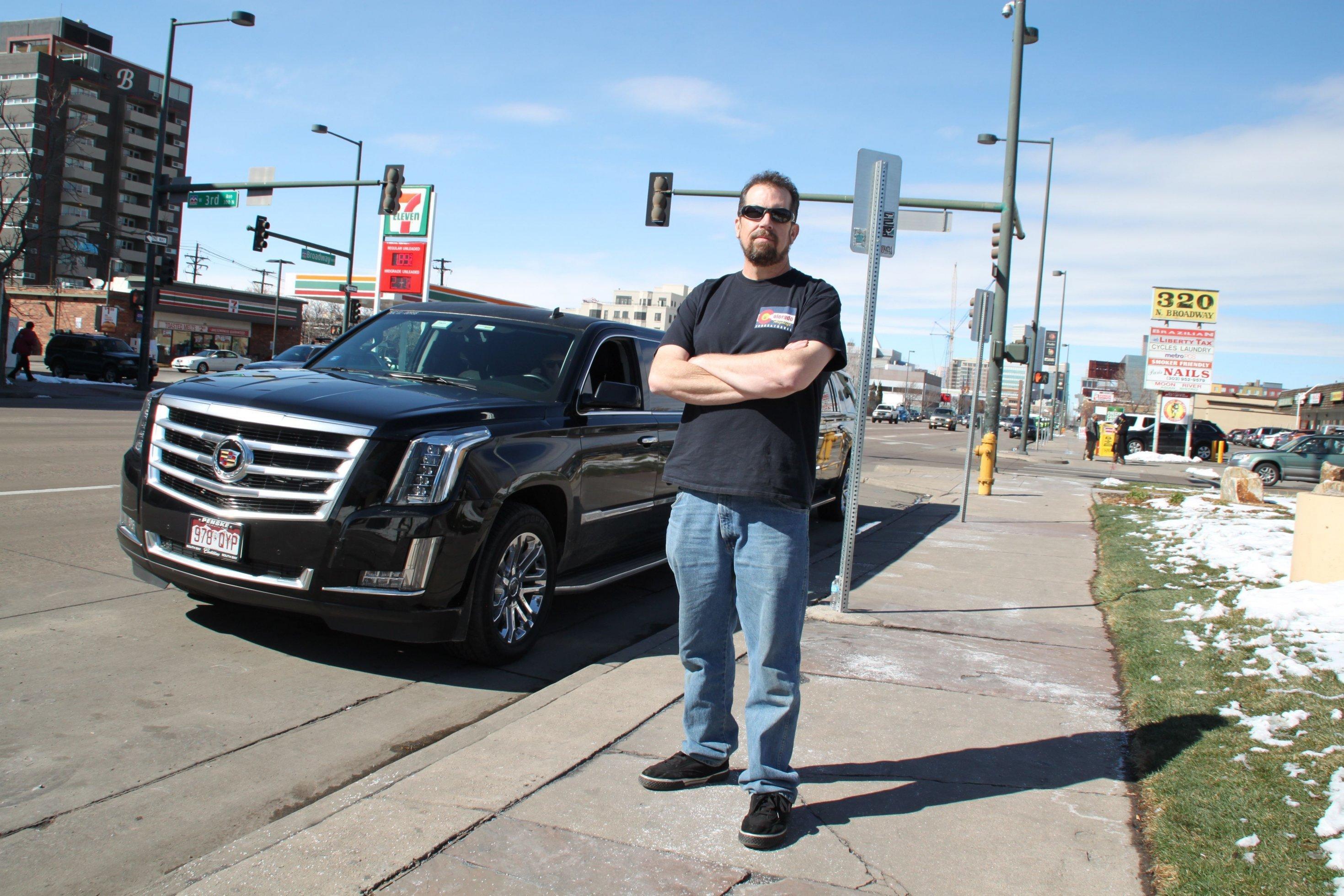 Ein Mann mittleren Alters steht vor einer Luxuslimousine.