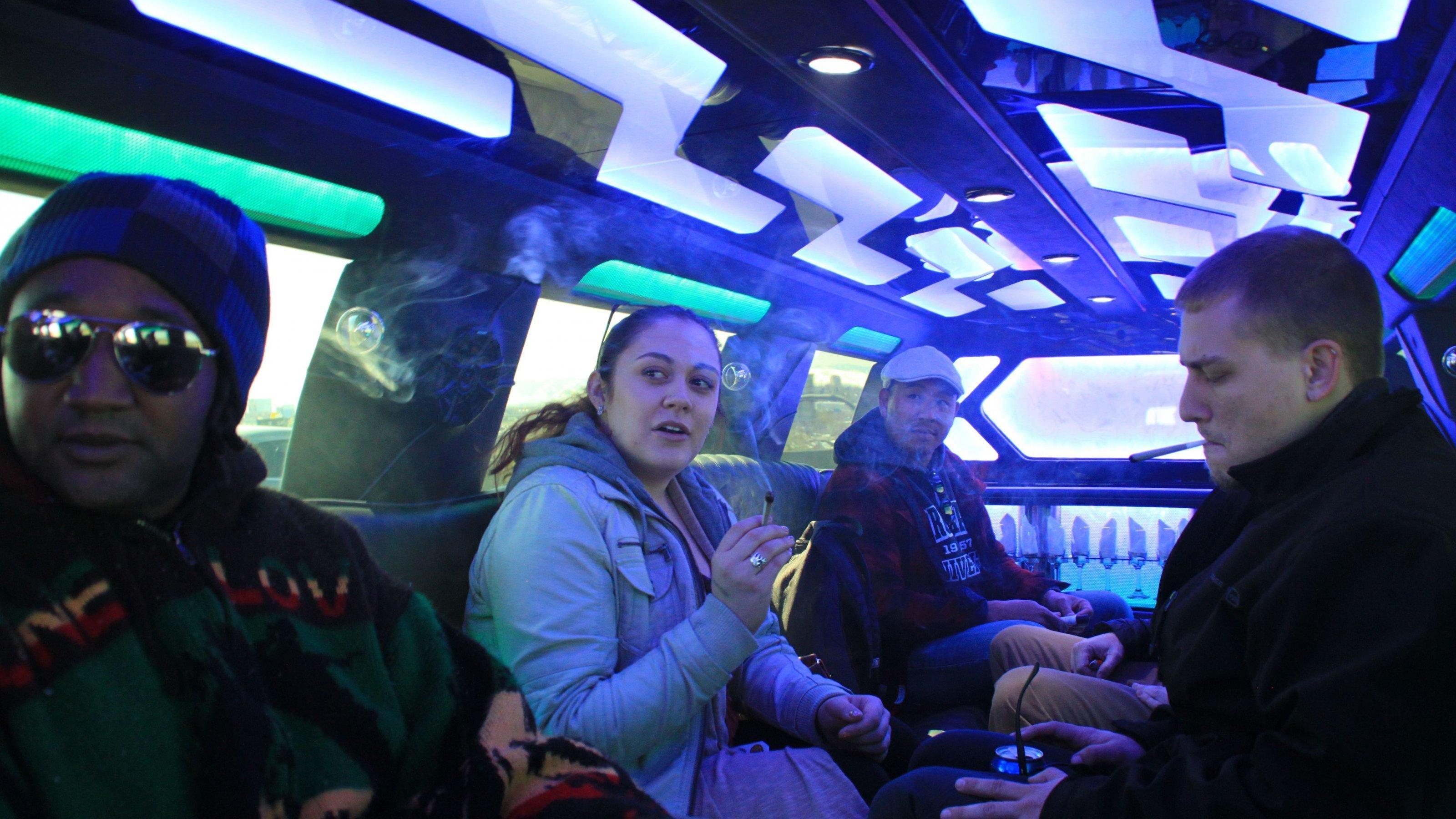 Vier junge Leute sitzen in einer Luxuslimousine und kiffen.