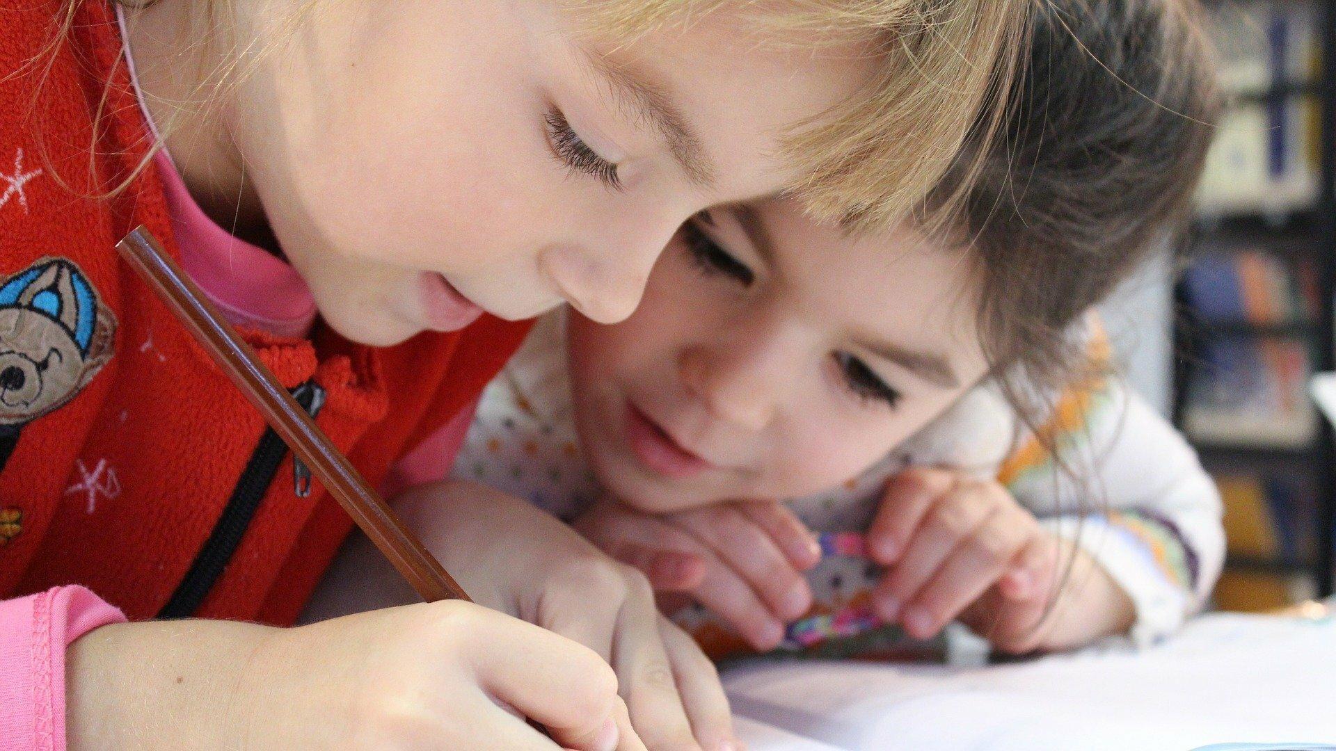 Zwei Mädchen beugen sich über ein Blatt Papier. Das eine Mädchen hat einen Stift in der Hand, mit dem sie malt.
