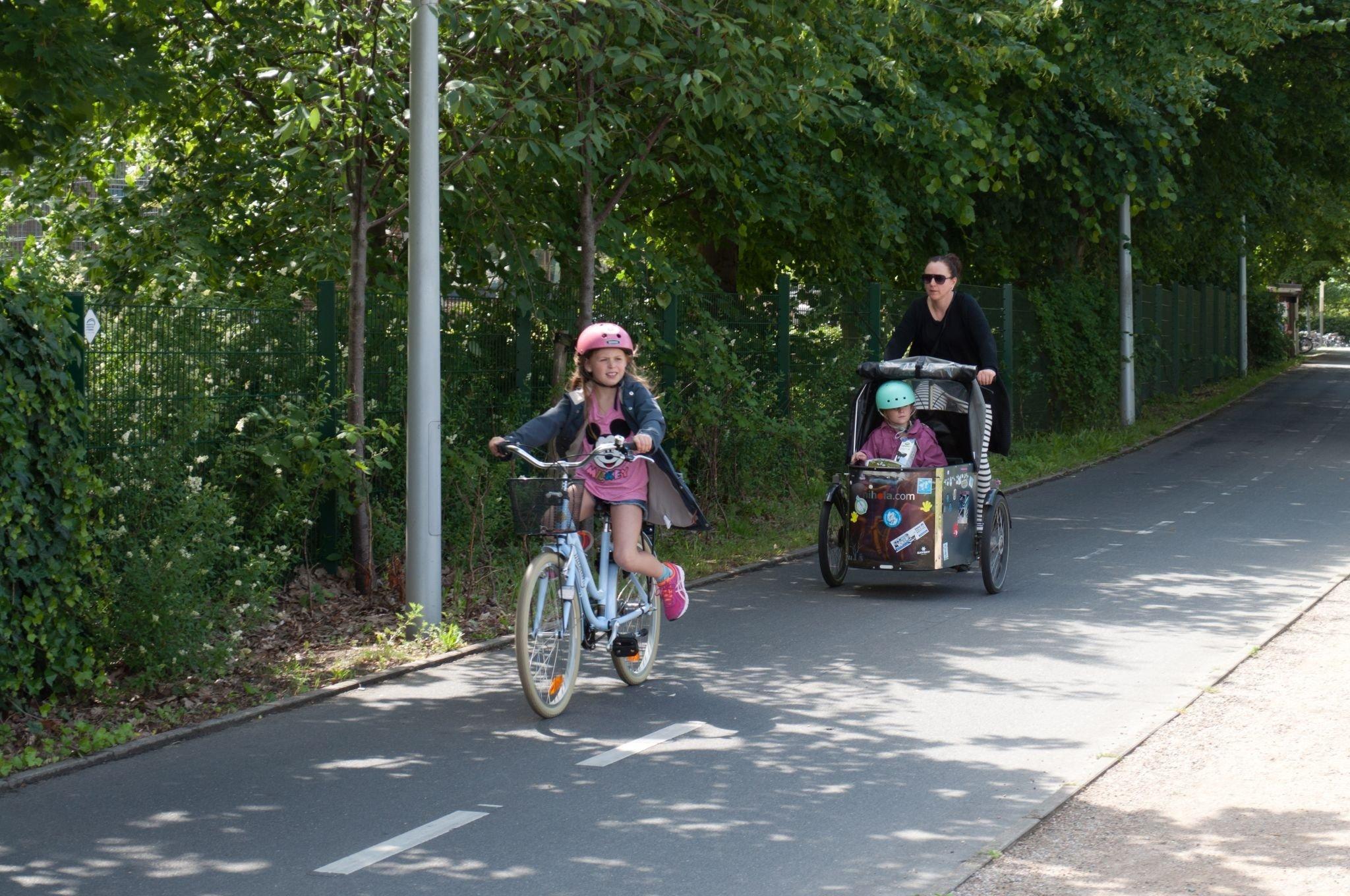 Ein kleines Mädchen fährt Fahrrad auf einem breiten Radweg. Einige Meter hinter ihr fährt die Mutter.