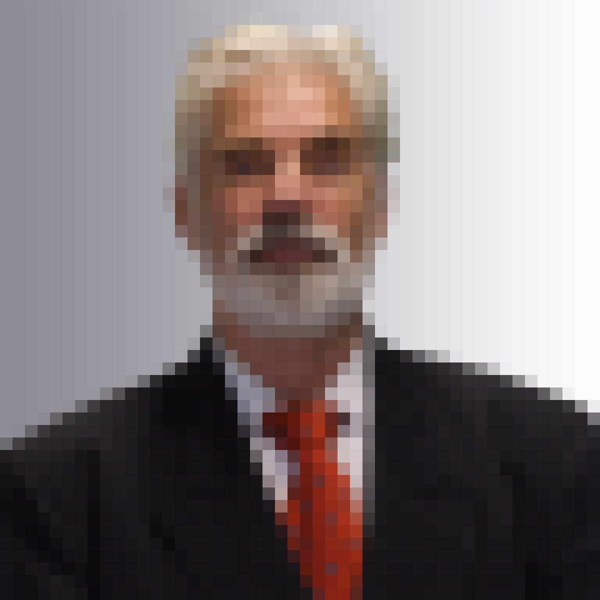 Das Bild zeigt einen weißhaarigen Mann mit Vollbart im Anzug mit roter Krawatte.