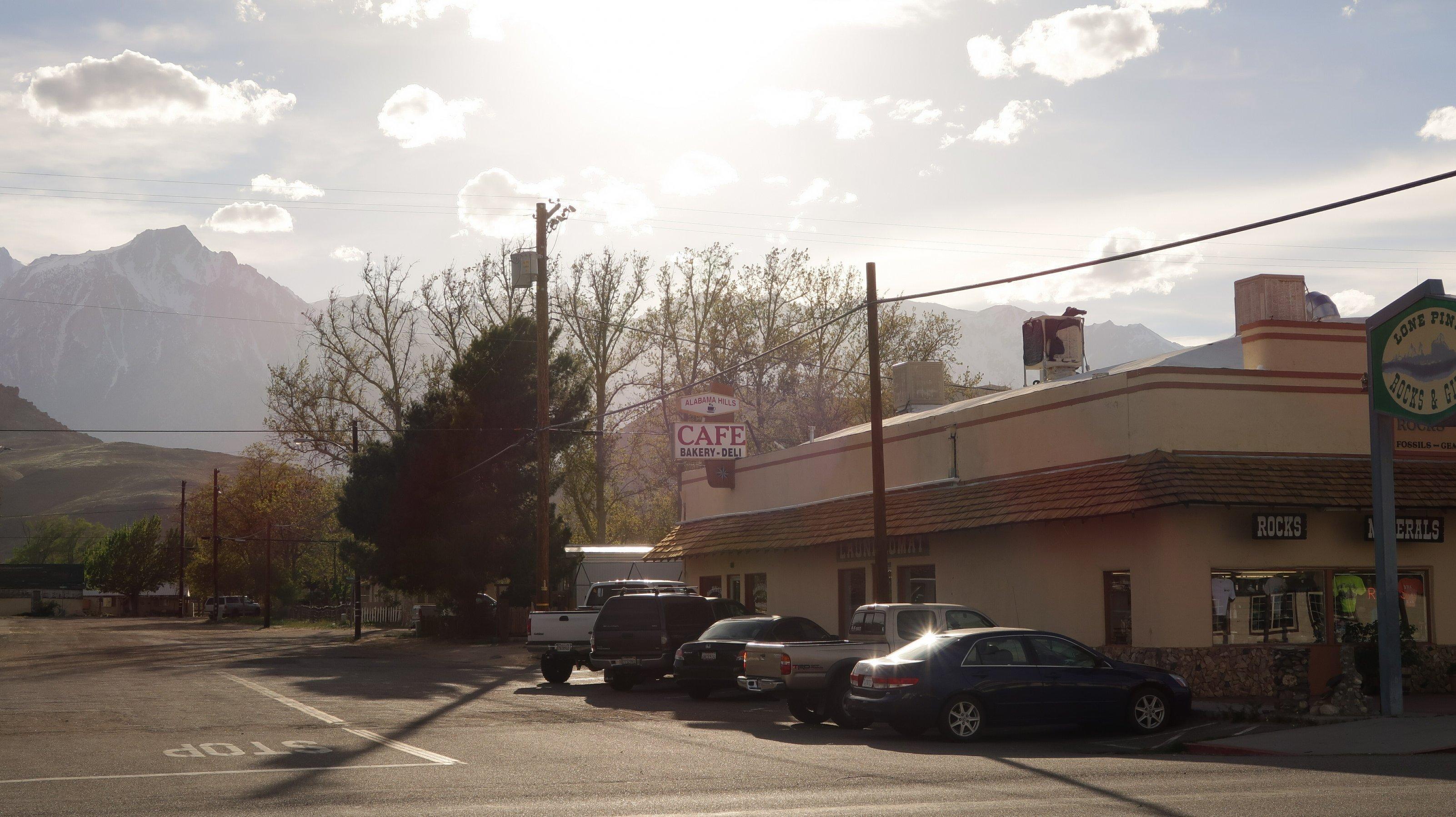 Vor einem Café parken Autos. Im Hintergrund ist ein Gebirge zu sehen.