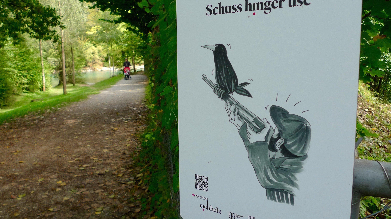 """""""Der Schuss geht nach hinten los"""": Mit humoristischen Plakaten macht in Bern eine Ausstellung auf die Konflikte zwischen Mensch und Saatkrähen aufmerksam. Das Plakat zeigt einen Jäger, auf dessen Waffe eine Saatkrähe sitzt."""