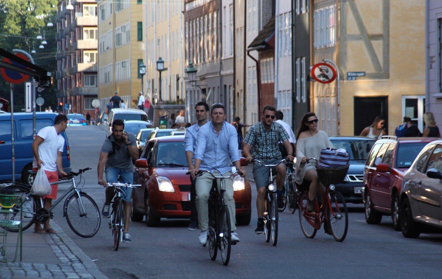 Auf einer kleinen Straße fahren viele Radfahrer. Hinter ihnen stauen sich einige Autos.