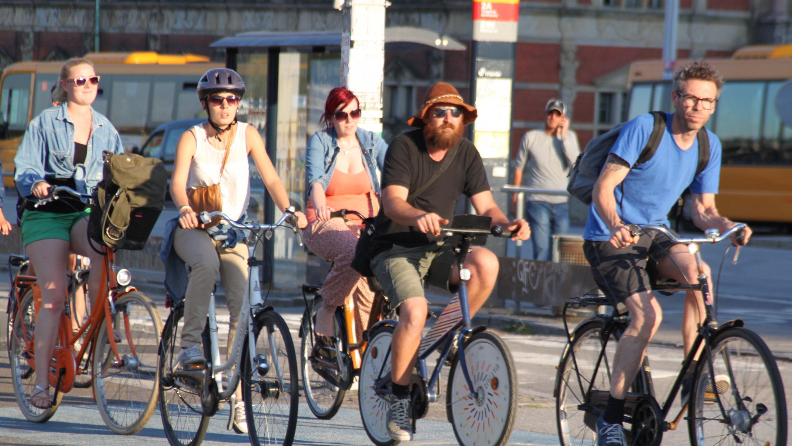 Fünf Radfahrer überqueren auf einem breiten blau gefärbten Radweg entspannt eine Kreuzung.