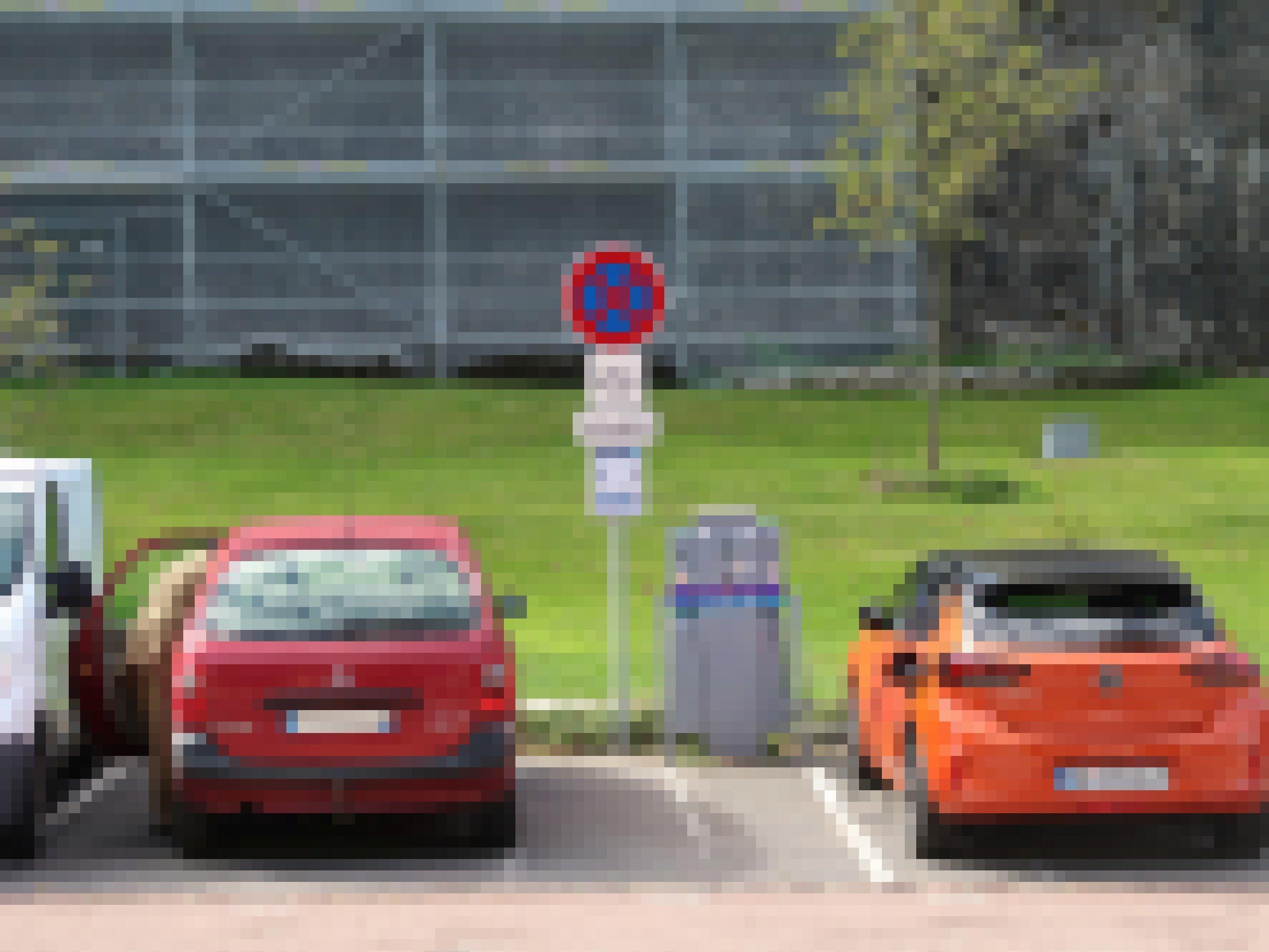 Zwei Auto stehen auf einem Parkplatz, eines davon ist an einer Ladestation angeschlossen.