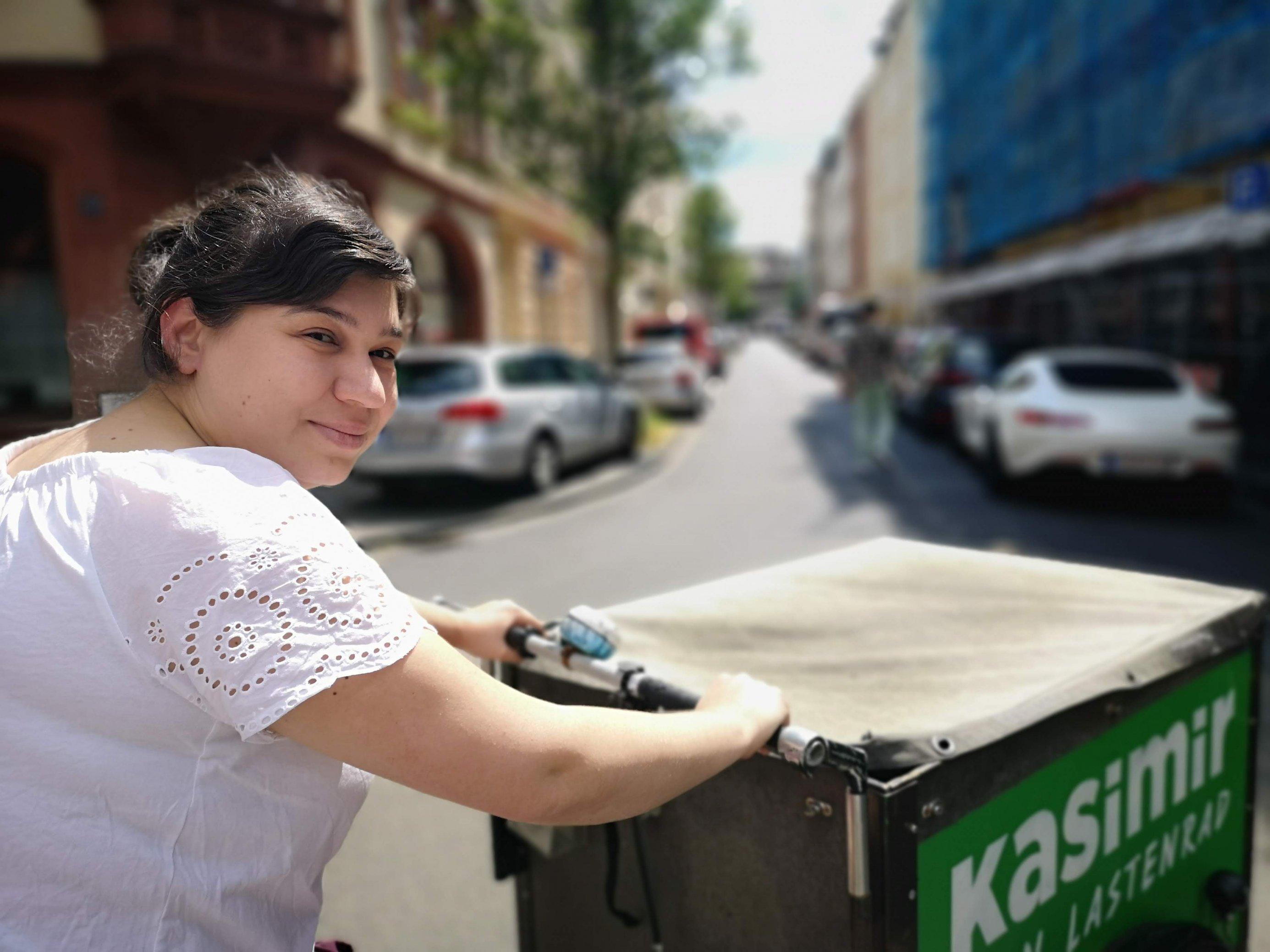 Fatma Erkus sitzt auf dem Lastenrad und blickt seitlich in die Kamera. Über ihre Schulter hinweg ist die große Box des Lastenrads von oben erkennbar. Sie wird mit einer Persenning gegen Regen geschützt