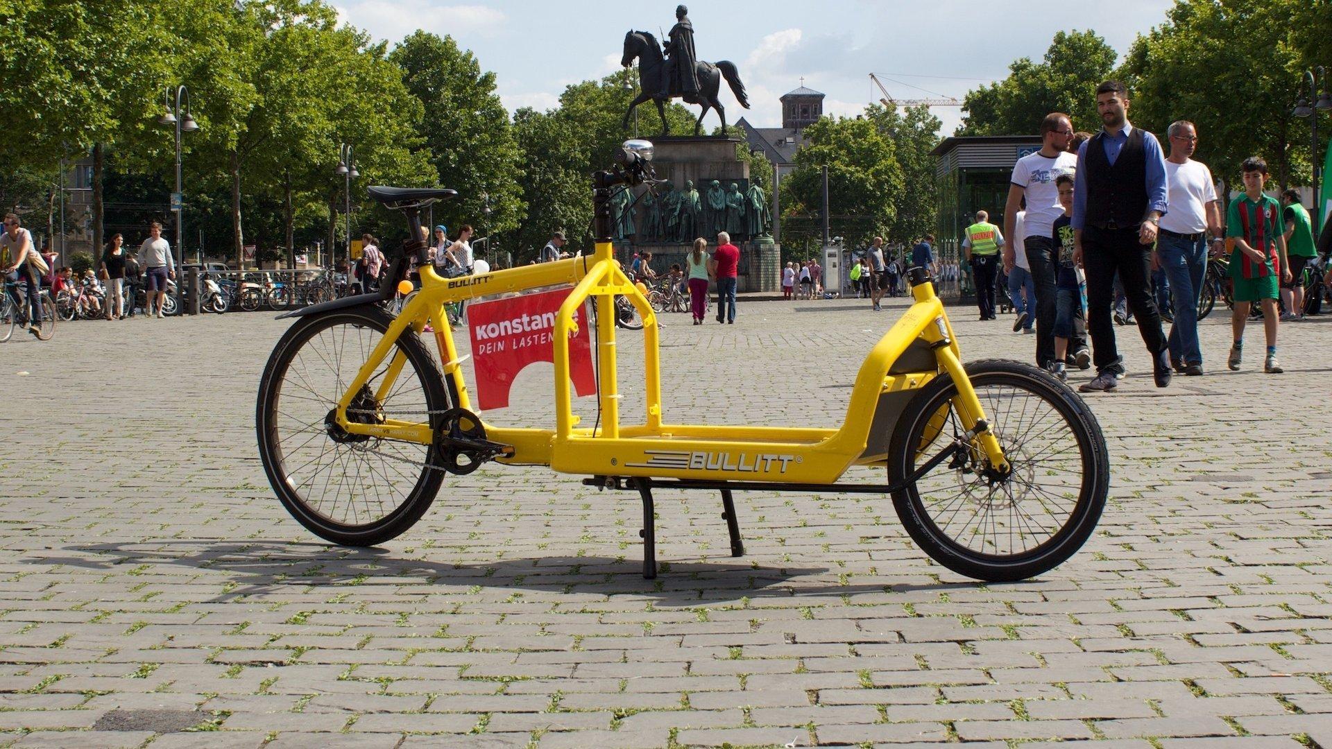 Das gelbe Lastenrad hat nur zwei Räder und fährt sich wie ein herkömmliches Fahrrad. Die Last kann vor dem Lenker befestigt werden. Es hat keine Box.
