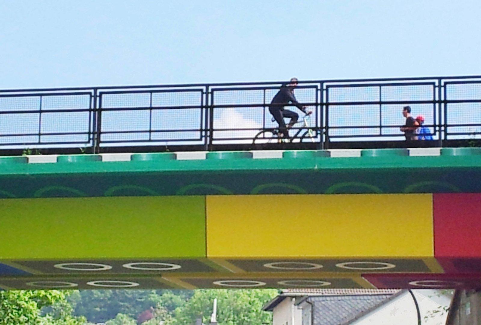 Ein Ausschnitt der Lego-Brücke, auf der ein Radfahrer und zwei Fußgänger hinter dem Geländer zu sehen sind. Der Himmel ist blau.