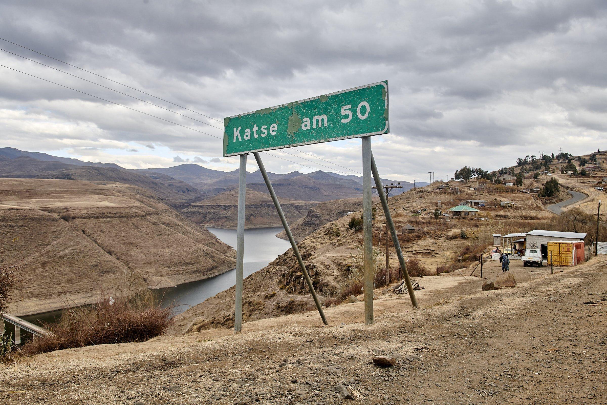 Über dem Tal mit dem Stausee steht ein Straßenschild mit der Aufschrift: Katse Dam 50km