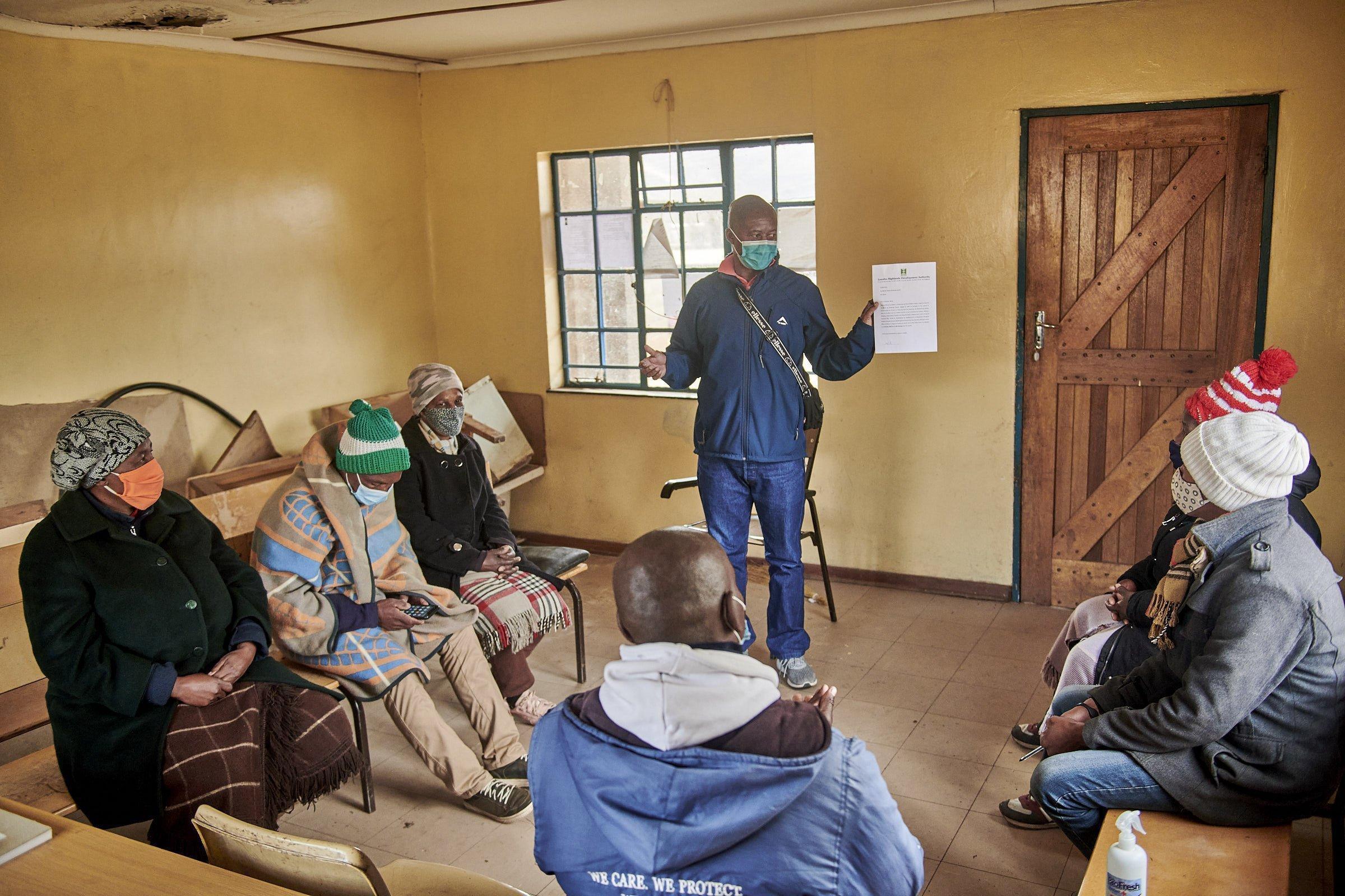 In einem Raum sitzen die Komitee-Mitglieder auf Bänken, vor ihnen hält Mothusi Sequee ein neues Schreiben der LHDA hoch