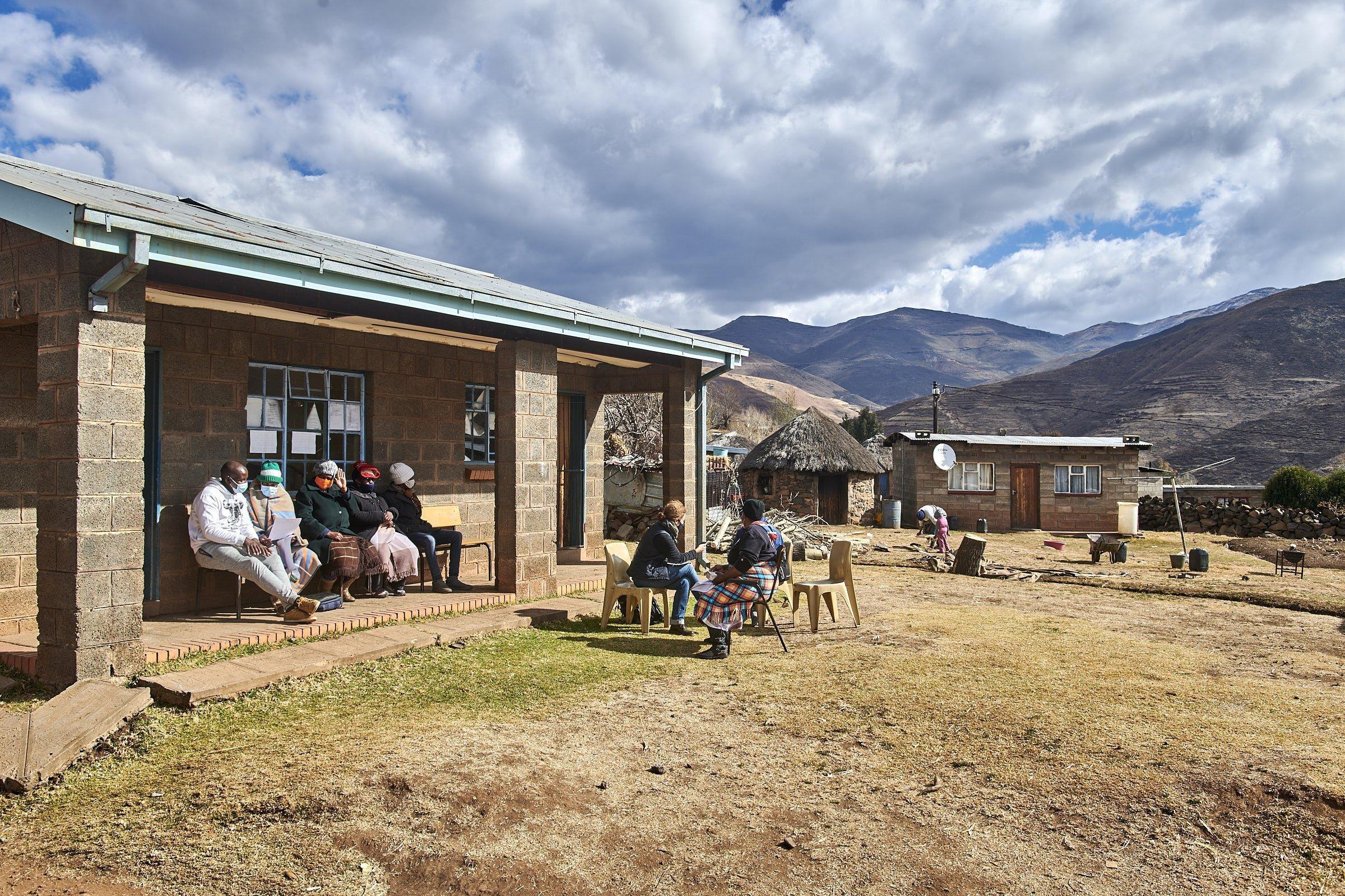 Vor einem kleinen Haus sitzen Bürger und Bürgerinnen, traditionelle Rundhütten und die Berge im Hintergrund