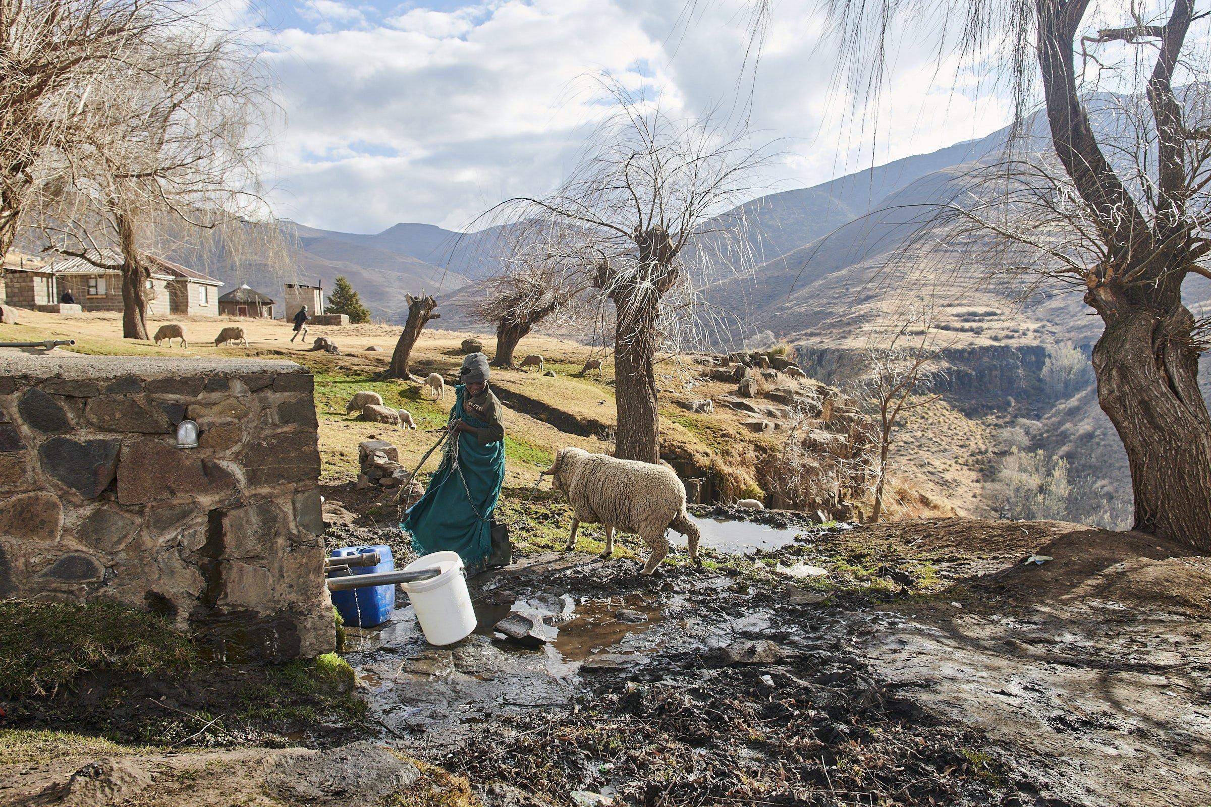 Ein Hirtenjunge und sein Schaf gehen durch den Matsch an der Wasserquelle vorbei