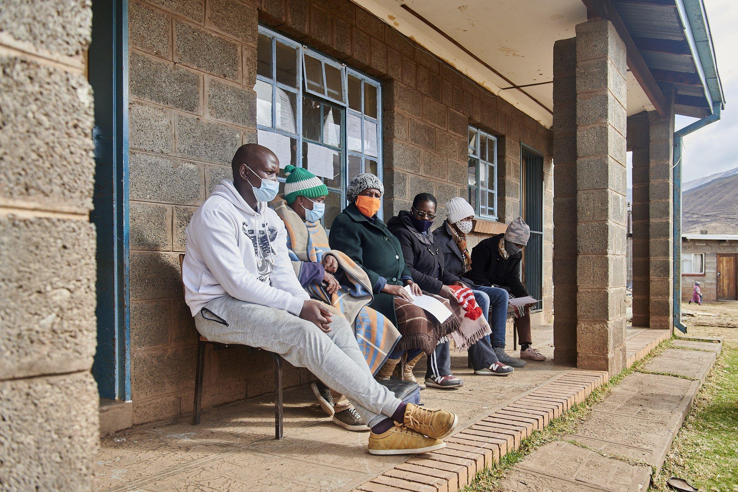 Vor einem kleinen Haus sitzen die Mitglieder des Komitees nebeneinander, sie tragen Corona-Masken und Mützen
