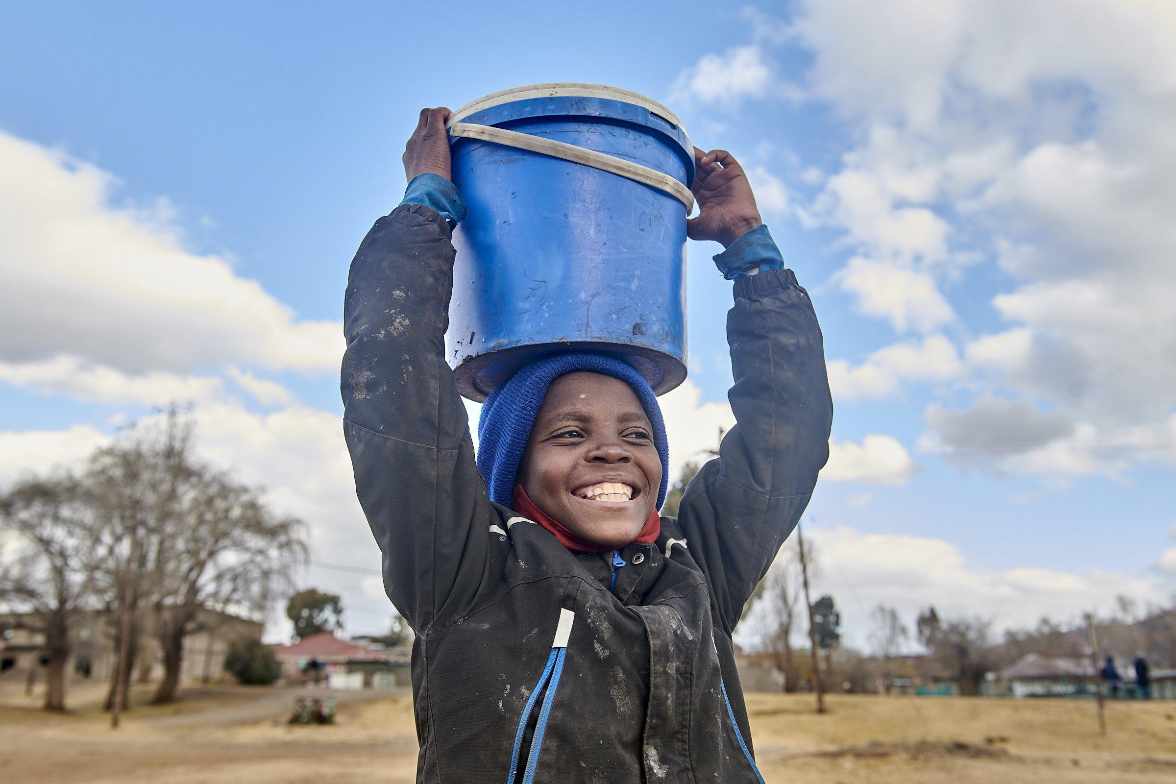 Das Mädchen strahlt über das ganze Gesicht, mit den Händen hält sie den blauen Wassereimer auf ihrem Kopf fest