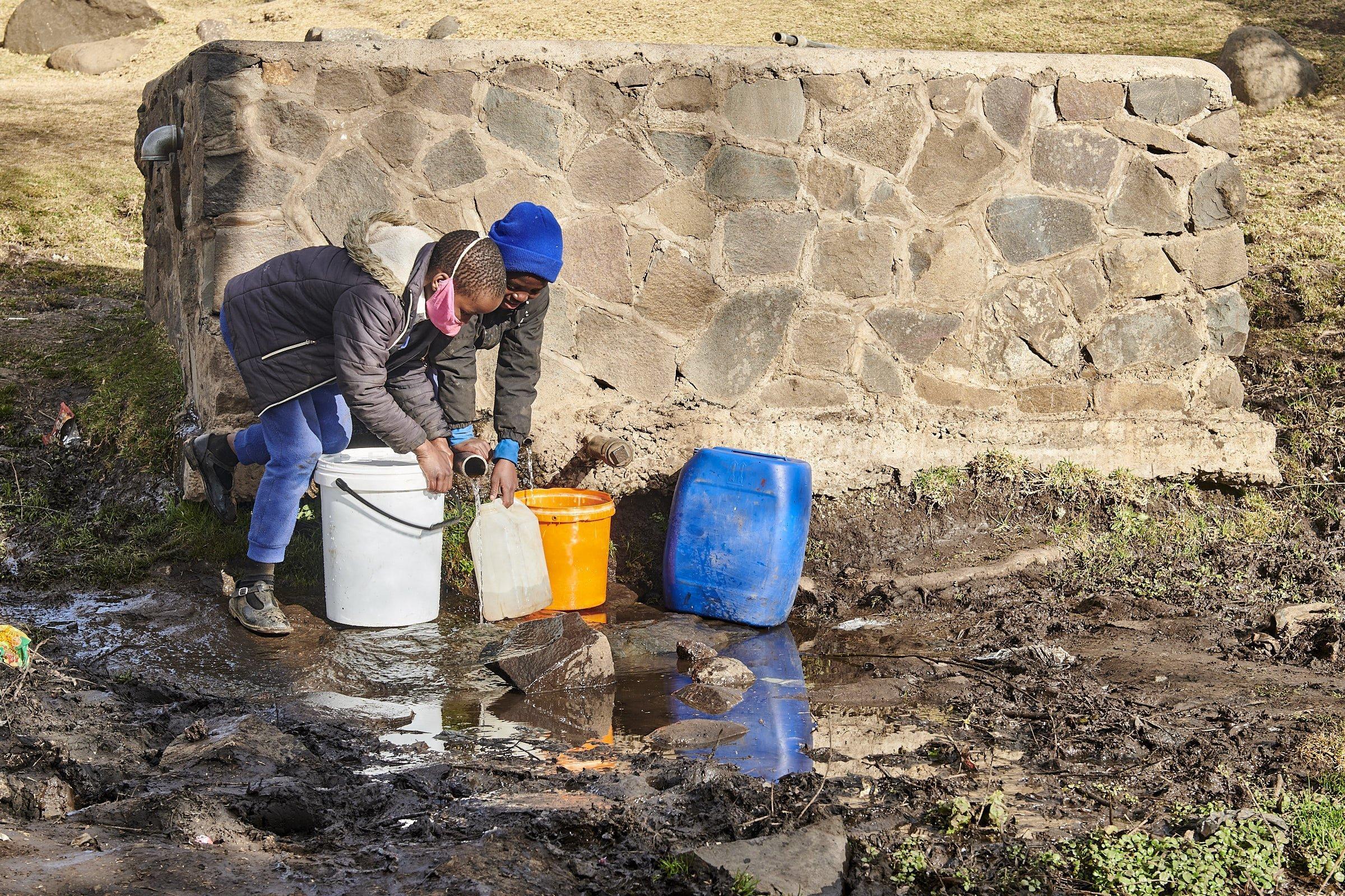 Zwei Mädchen stehen mit mehreren Wasserkanistern an der Wasserquelle – einem Steinquader aus dem zwei Rohre ragen