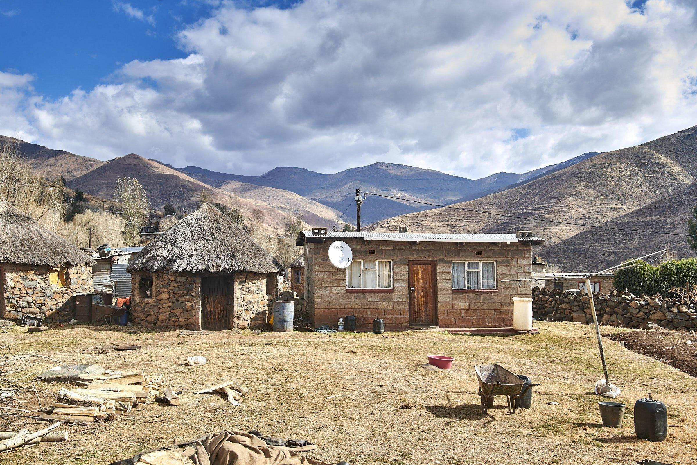 Ein kleines rechteckiges Haus mit Wellblechdach steht neben einem traditionellen Rundhaus – grasgedeckt, aus Naturstein