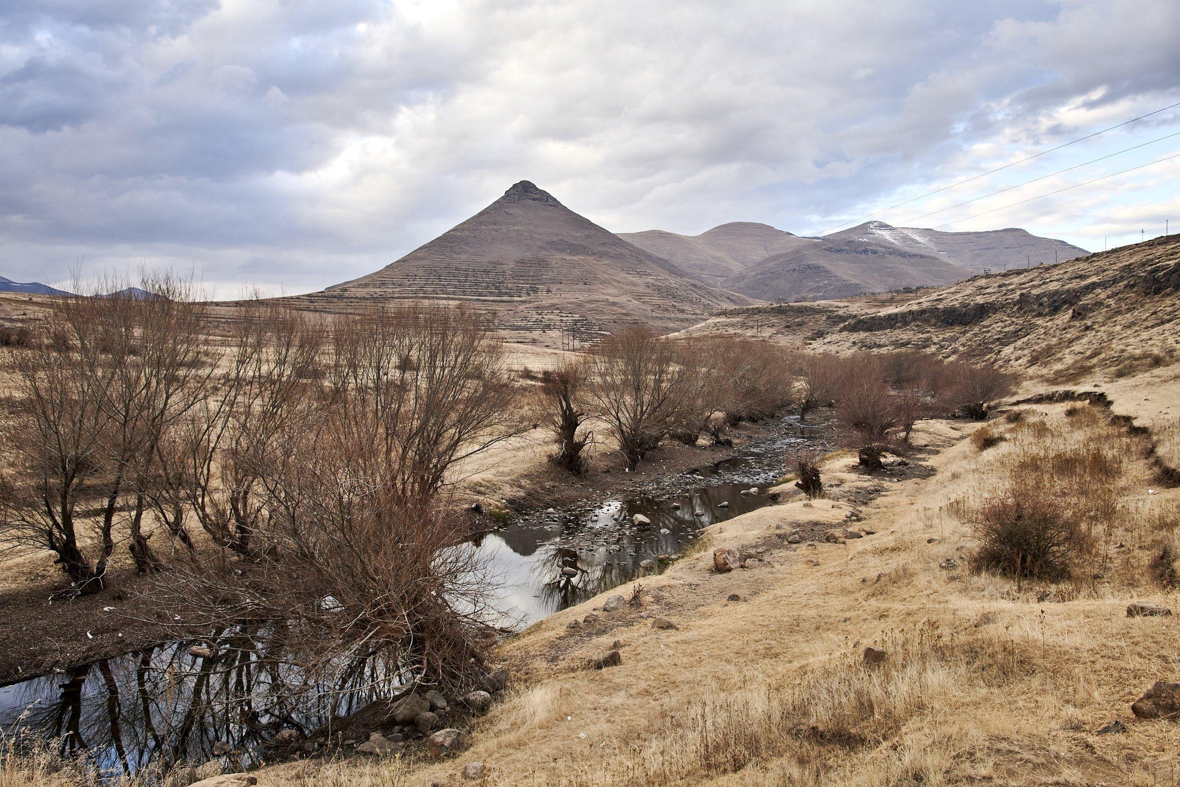 An dem Flussufer im Hochland Lesothos ist Erosion sichtbar, dahinter ragt ein pyramidenförmiger Berg in den Himmel