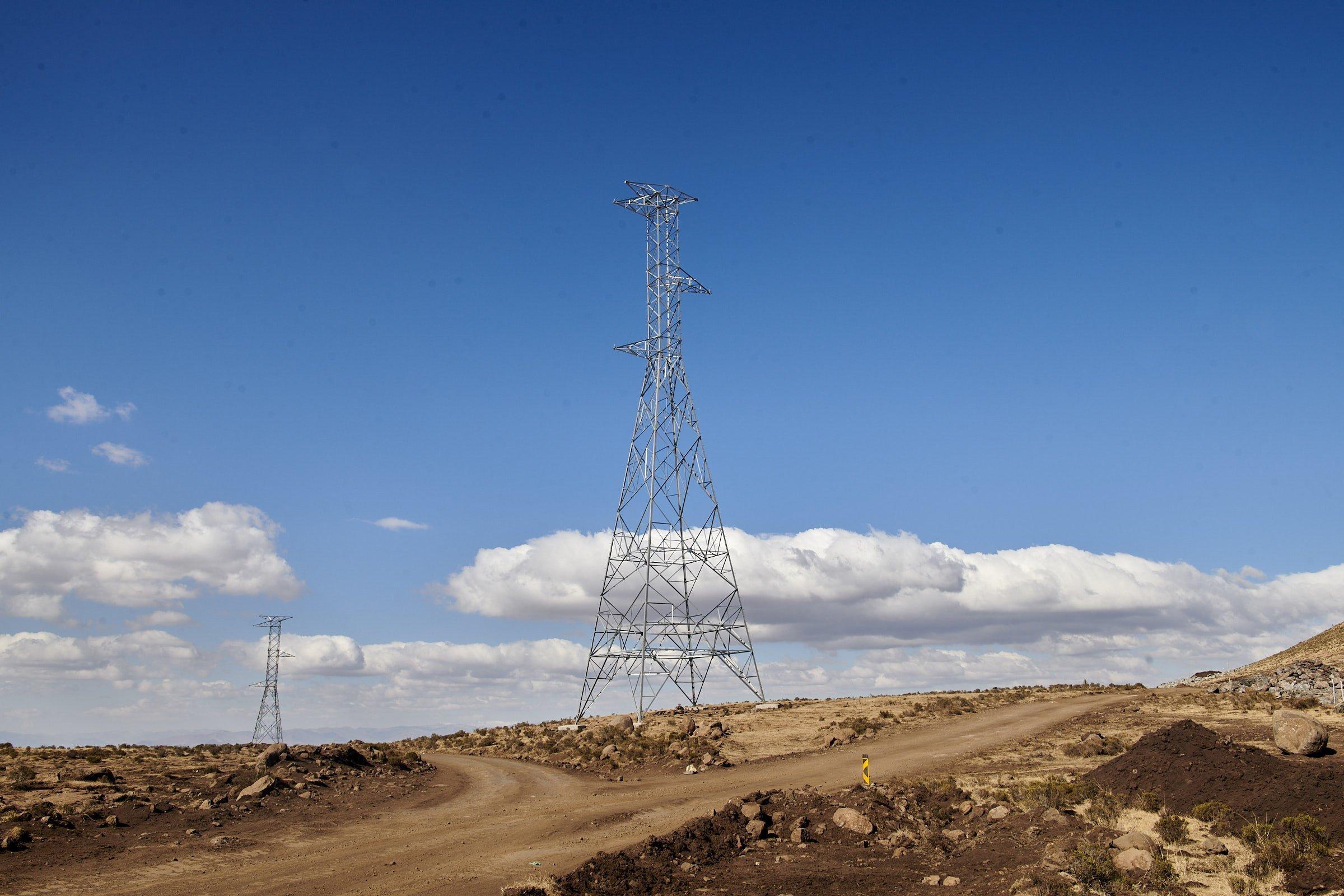 Hochspannungsmasten stehen in der Landschaft, die Überleitungen sind noch nicht installiert