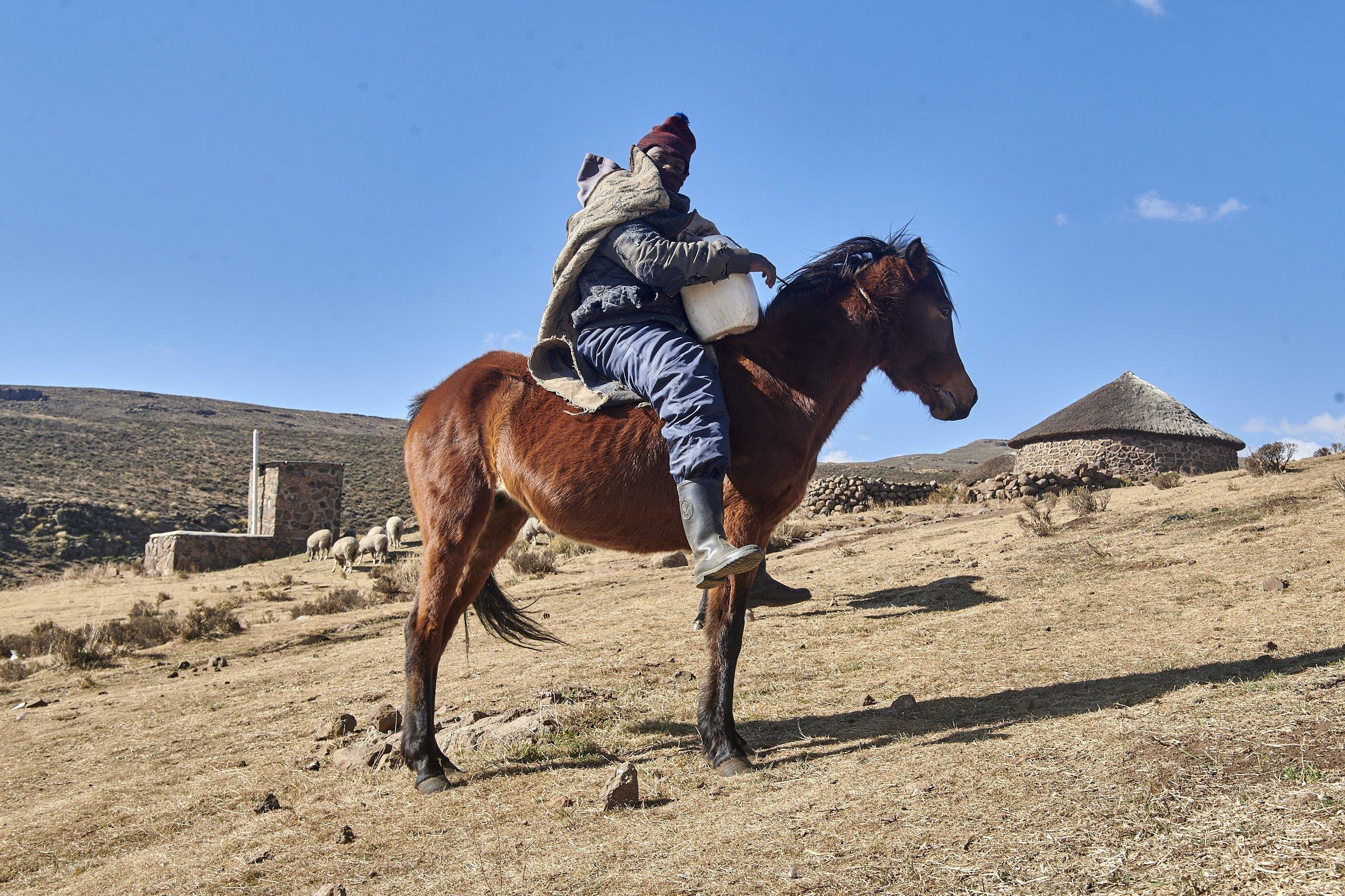 Der Reiter sitzt auf seinem braunen Pferd, einen Wasserkanister vor der Brust