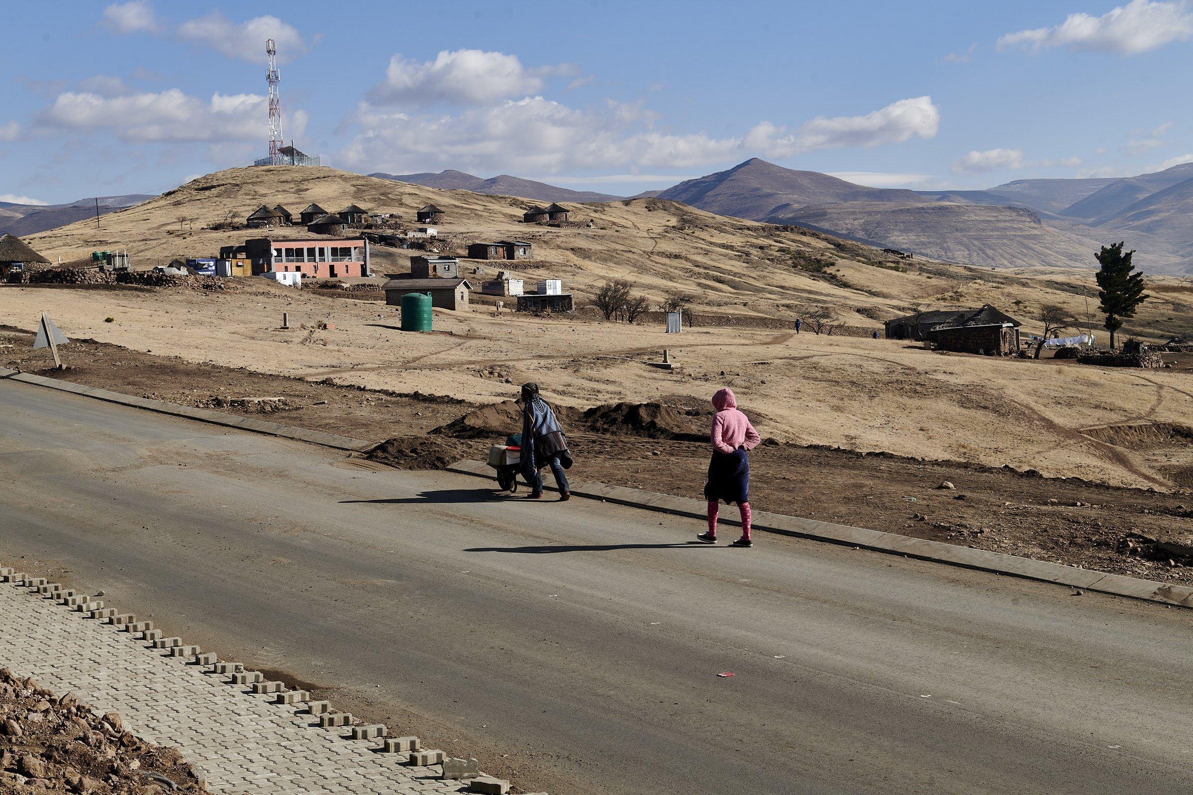 Auf der neuen Straße schiebt eine Frau eine Schubkarre, eine andere folgt ihr. Neben Rundhäusern sind nun auch neue Gebäude für die Arbeiter des Wasserprojekts gebaut worden