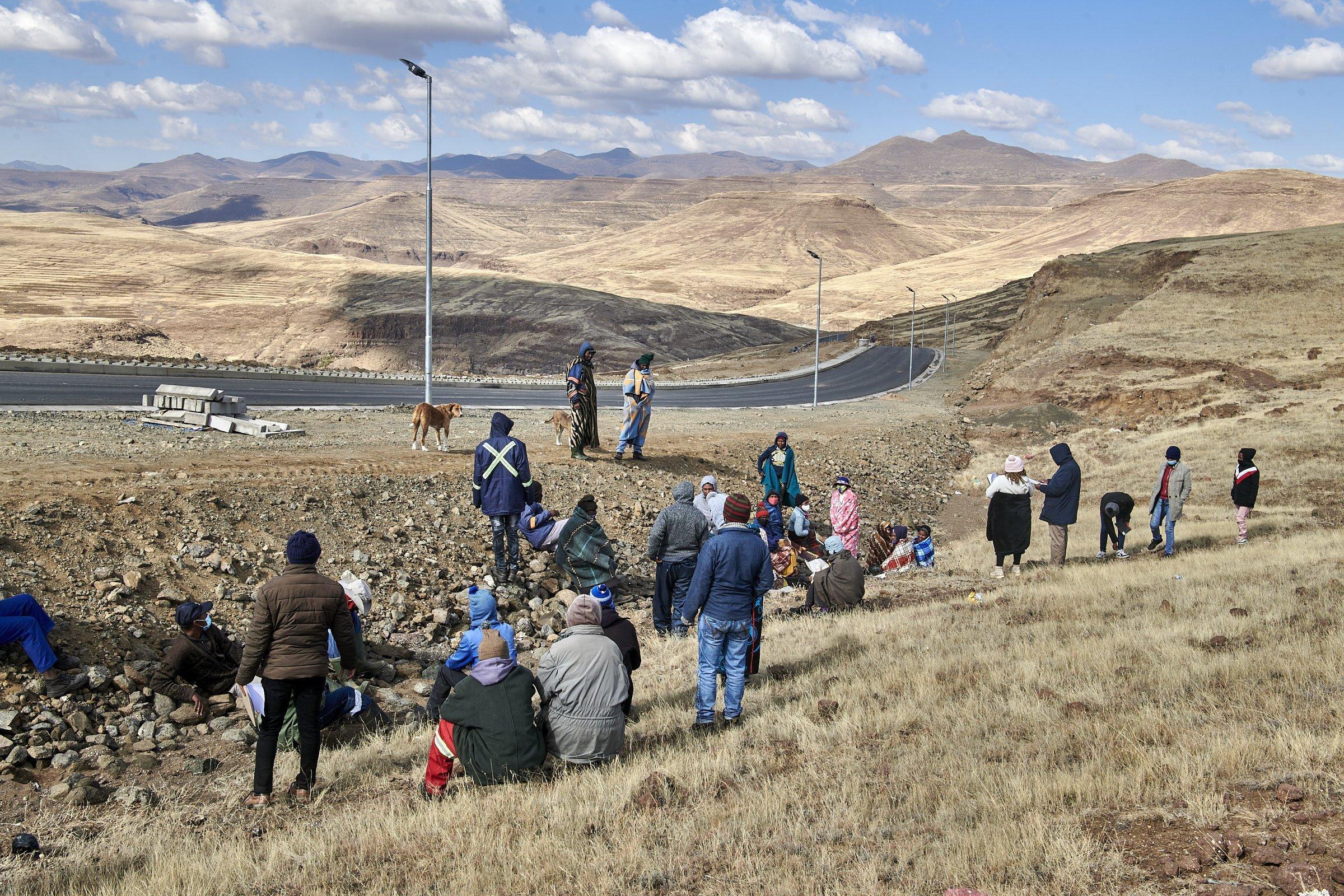 Am Feld am Rand der neuen Teerstraße haben sich die Dorfbewohner zu einem Krisentreffen versammelt, einige stehen, andere sitzen auf dem Boden