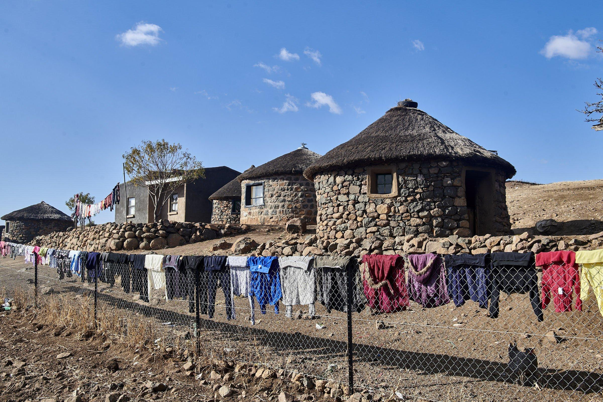 Über dem Zaun, der das Dorf von der Baustelle trennt, hängt Wäsche zum Trocknen in der Sonne