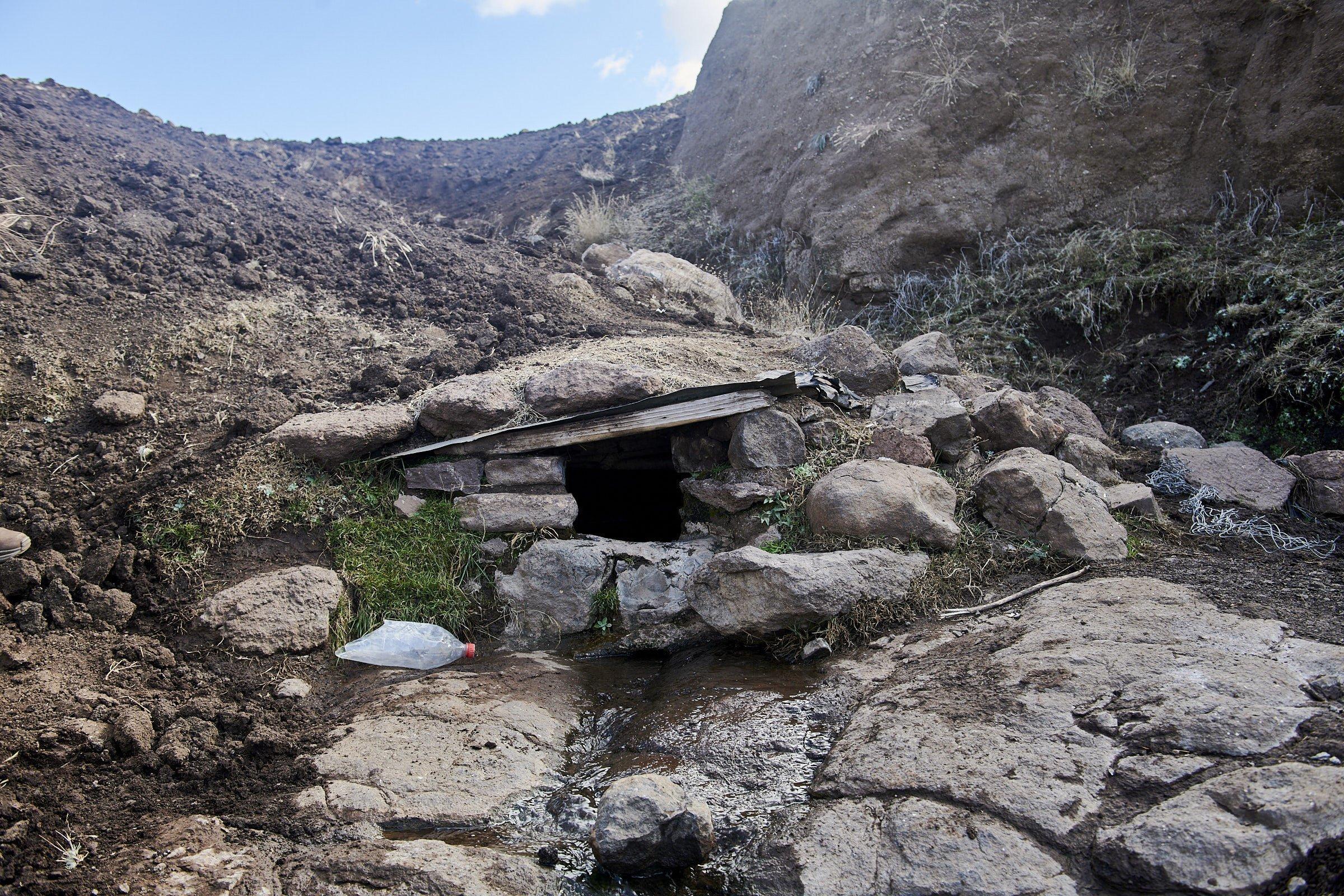 Unter einem kleinen Steindach kommt Quellwasser, daneben liegt eine leere Plastikflasche