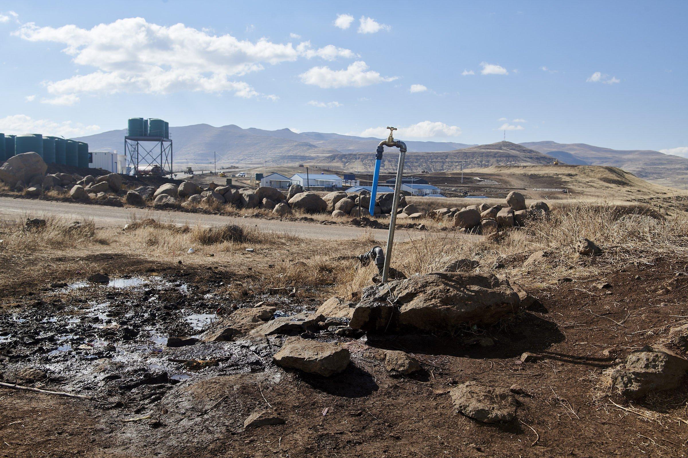 Ein Wasserhahn steht zwischen Steinen, im Hintergrund sind die Wassertanks der Baustelle zu sehen